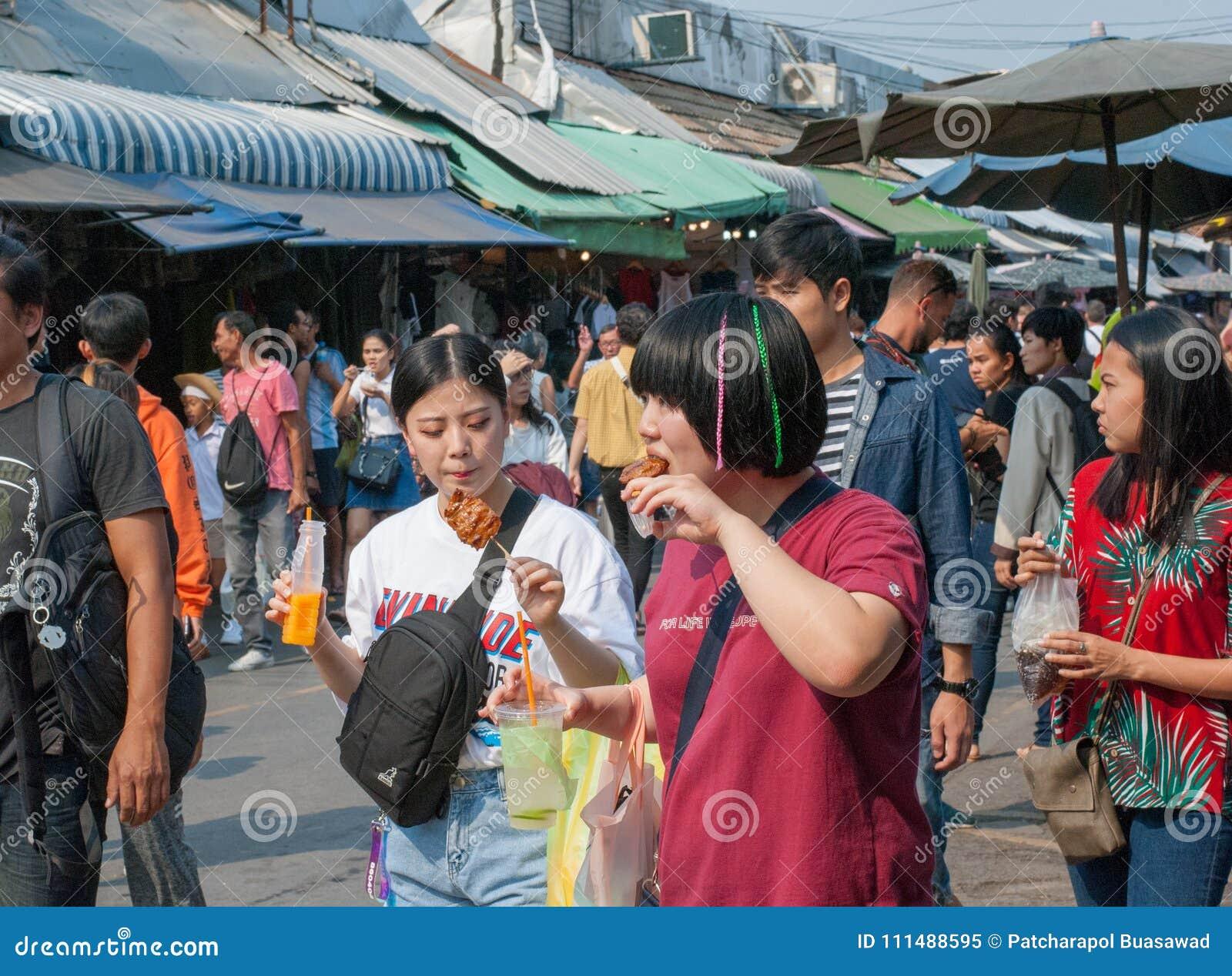 Amigos adolescentes asiáticos que andam e que comem algum alimento e que bebem o suco de fruto