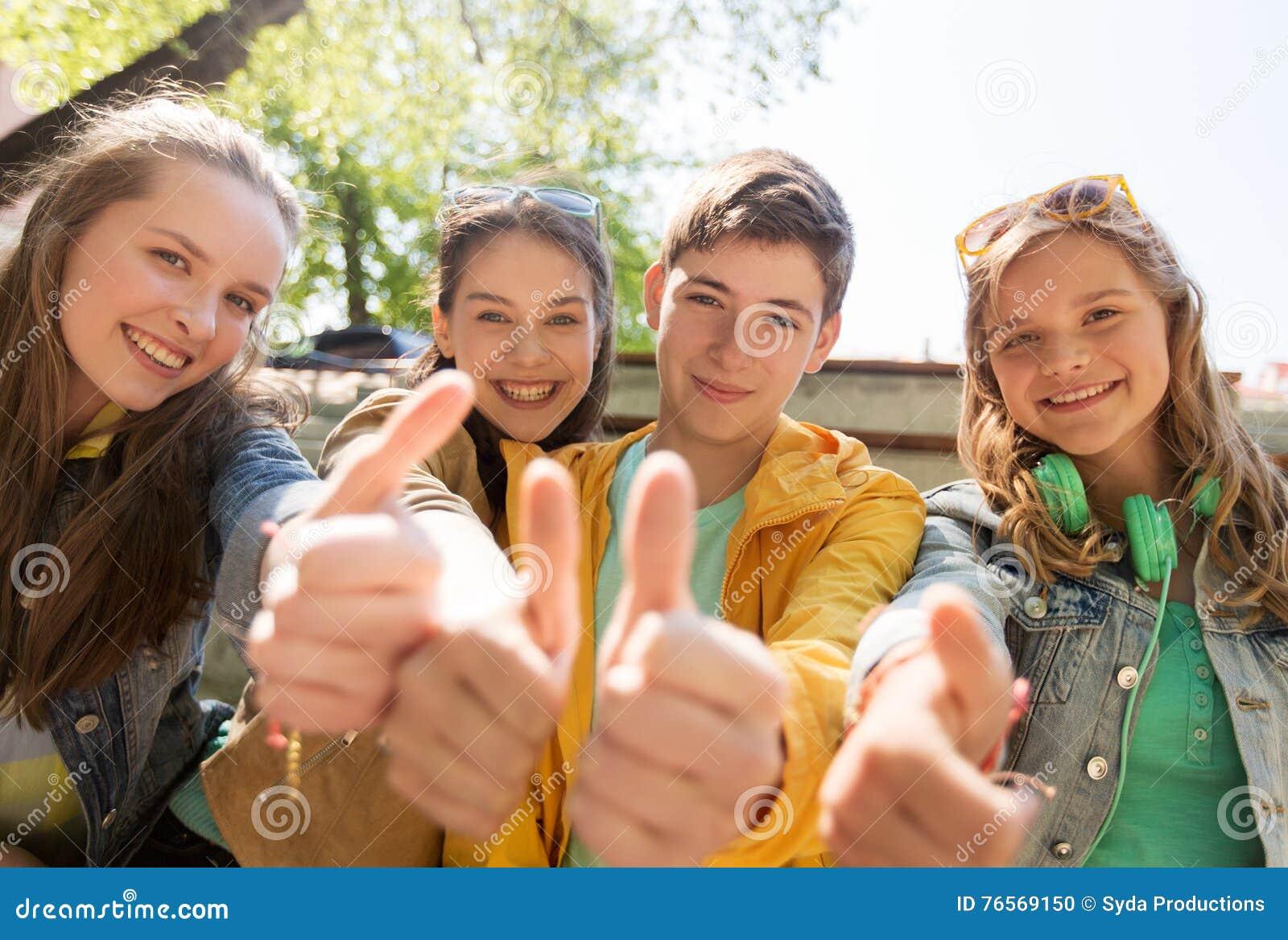 Amigos adolescentes ou estudantes que mostram os polegares acima