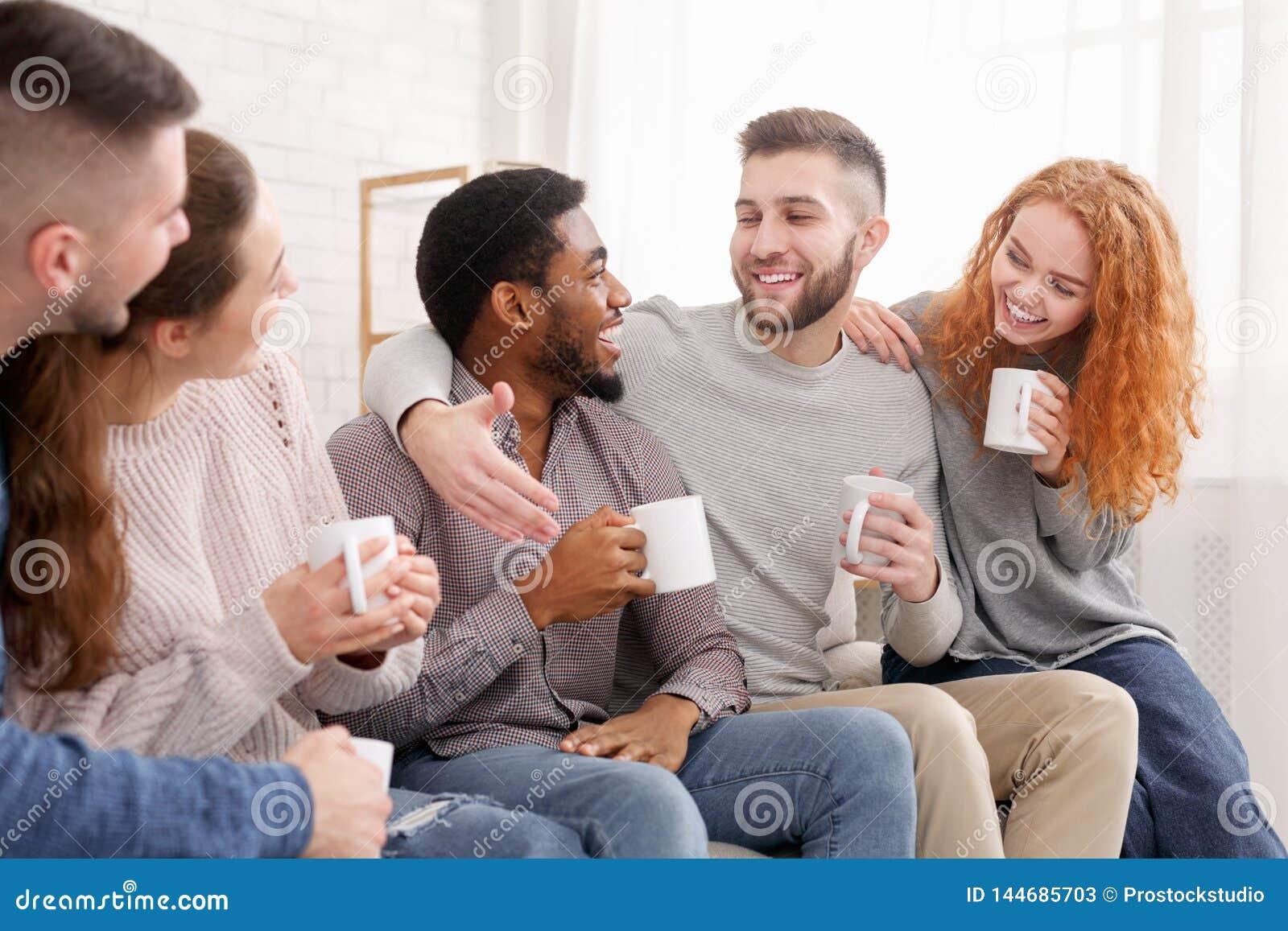 Amigos alegres que bebem o café e que apreciam sua empresa