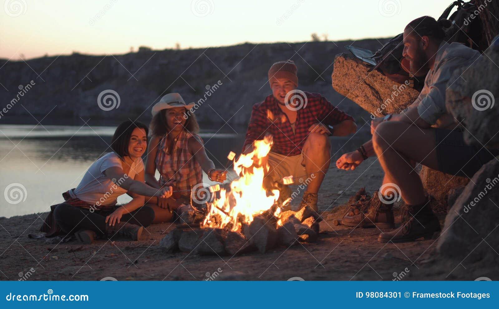 Amigos alegres que se relajan alrededor de hoguera