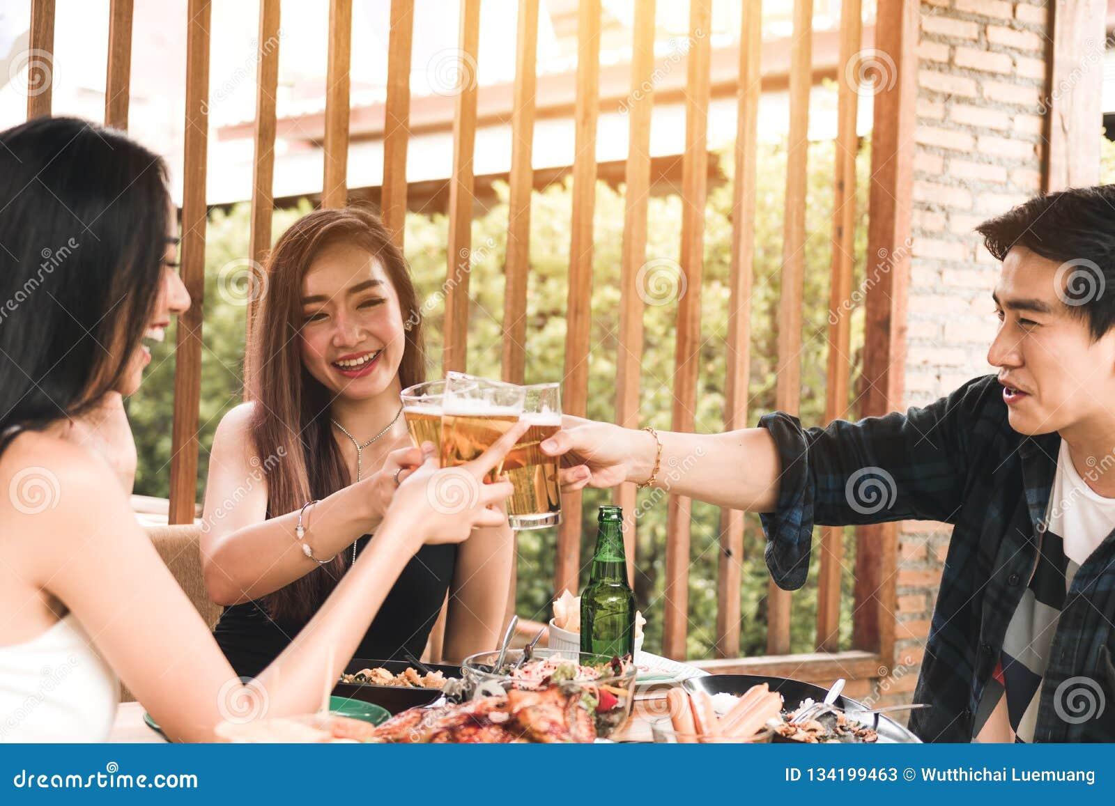 Amigos asiáticos de Teeneger que tintinean los vidrios mientras que disfruta de una cena en un restaurante