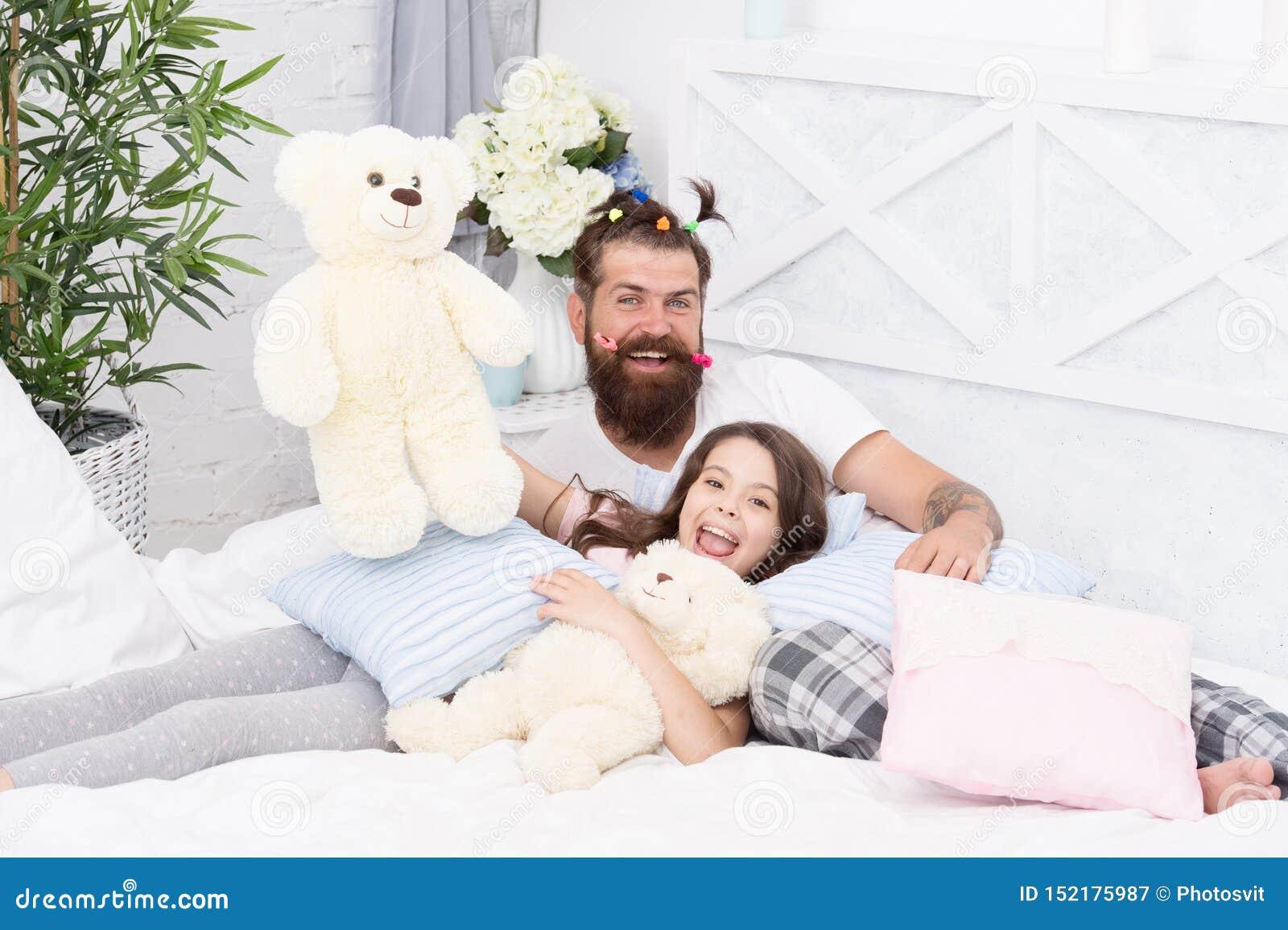 Amigos cercanos Papá y muchacha que se relajan en dormitorio Estilo de los pijamas Hombre barbudo del padre con las colas de caba
