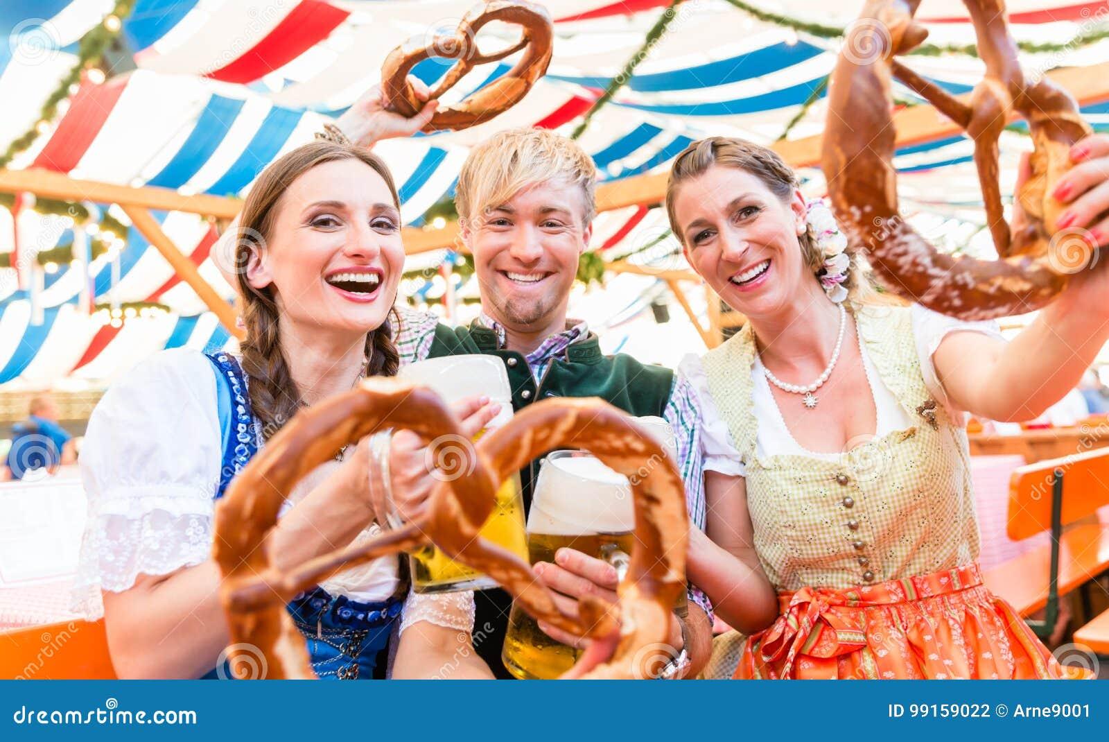 Amigos com os pretzeis gigantes na barraca bávara da cerveja