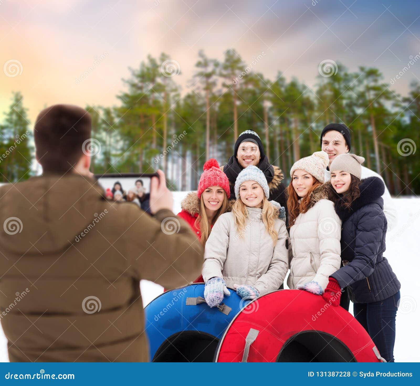 Amigos con los tubos de la nieve que toman la foto por la PC de la tableta
