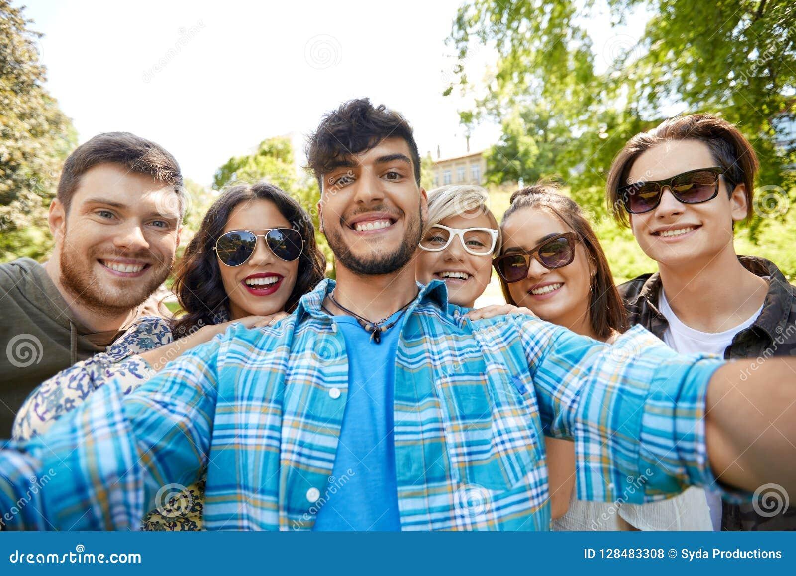 Amigos de sorriso felizes que tomam o selfie no parque do verão