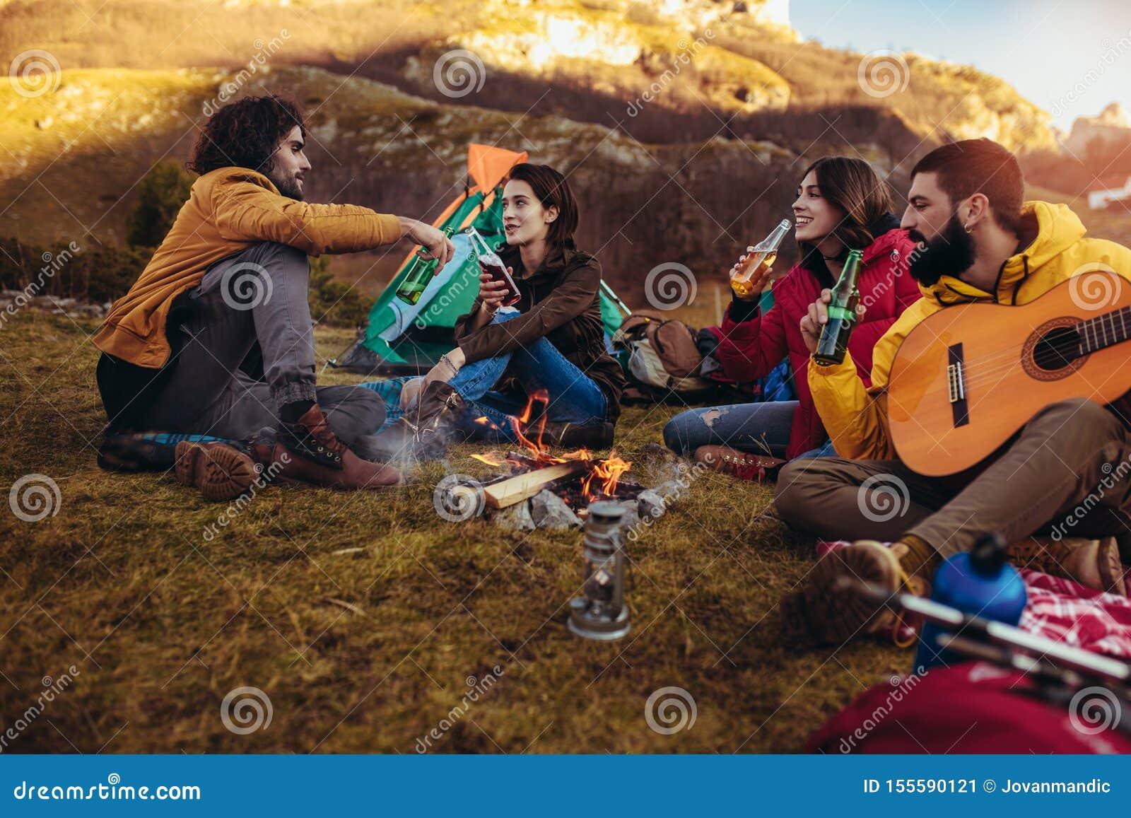 Amigos de sorriso que sentam-se em torno da fogueira no acampamento