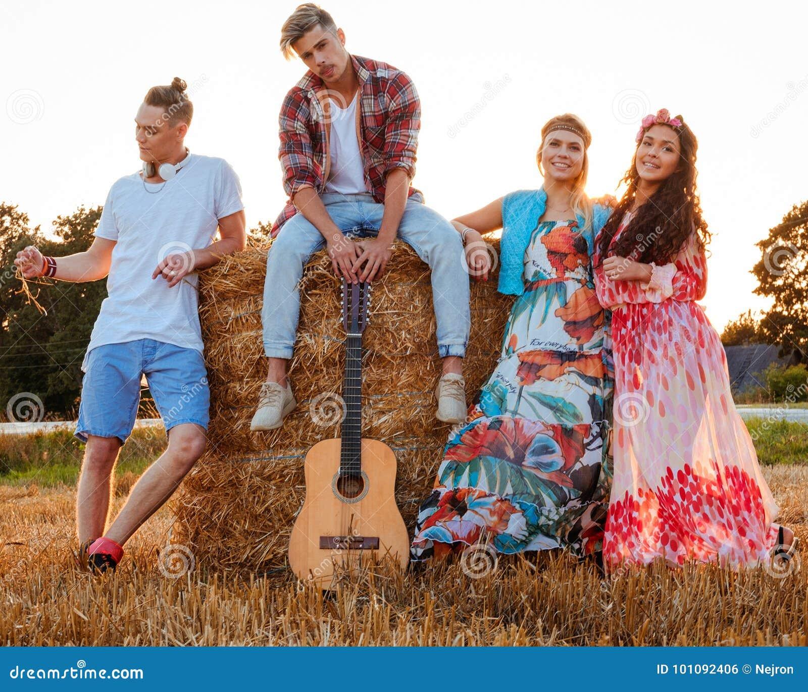 Amigos del hippie con la guitarra en un campo de trigo