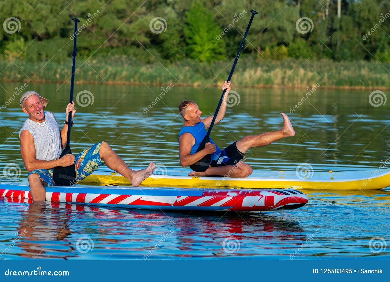 Amigos divertidos, personas que practica surf de un SORBO que ríen y que se divierten