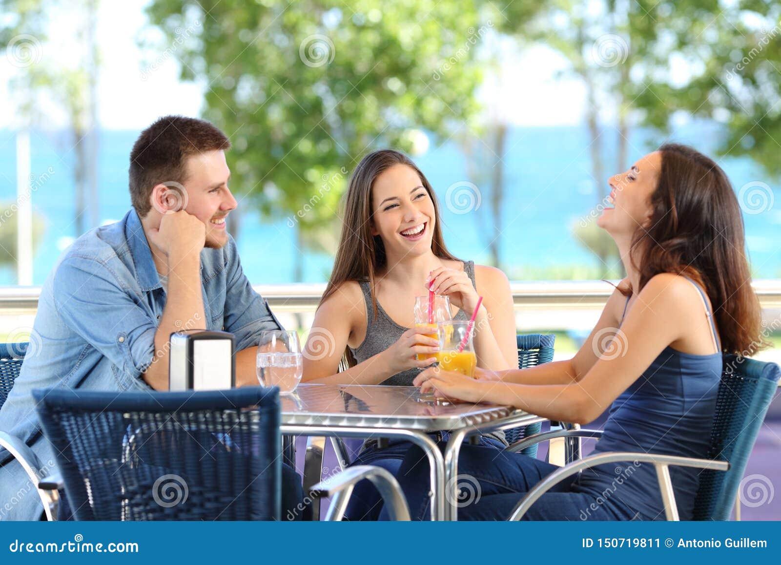 Amigos divertidos que hablan y que ríen en una barra o un hotel