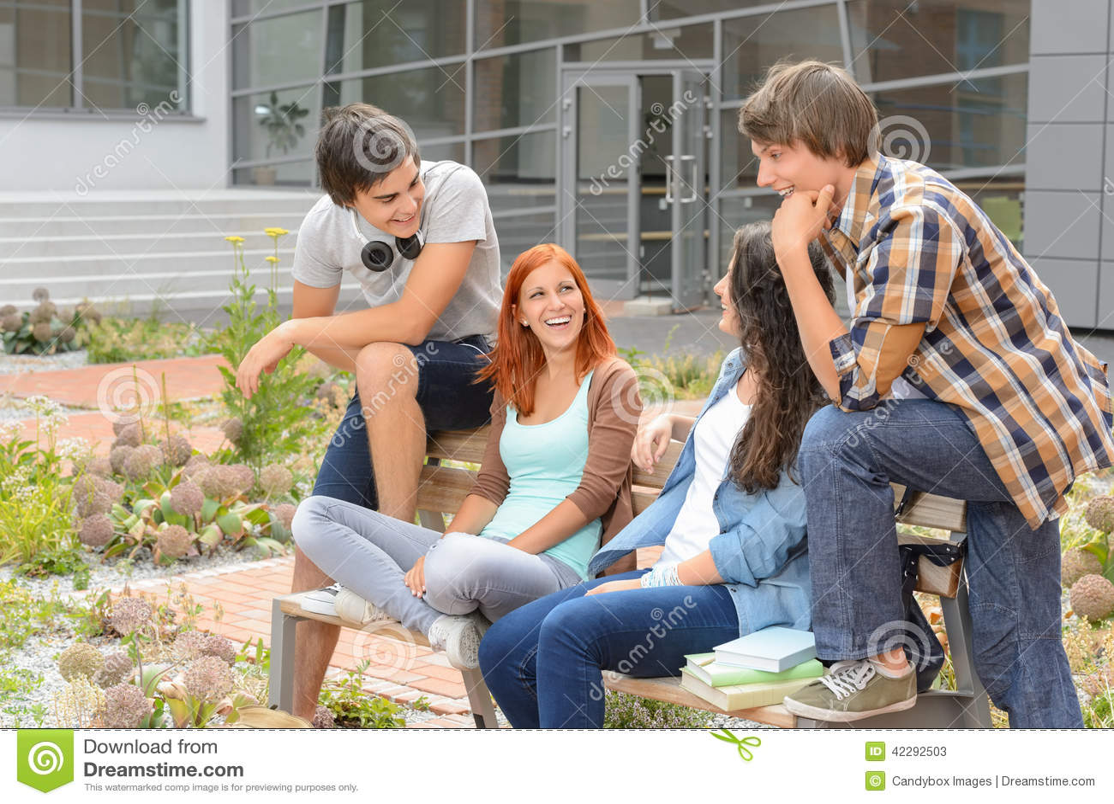 Amigos do estudante que sentam-se fora do riso do terreno
