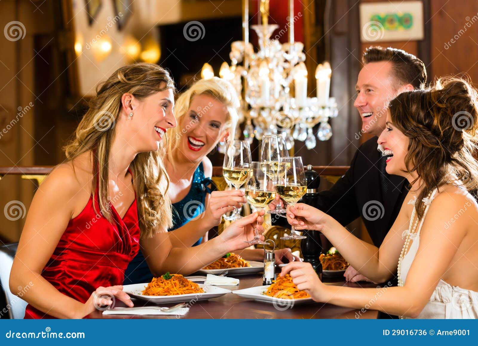 Amigos em vidros muito bons de um clink do restaurante