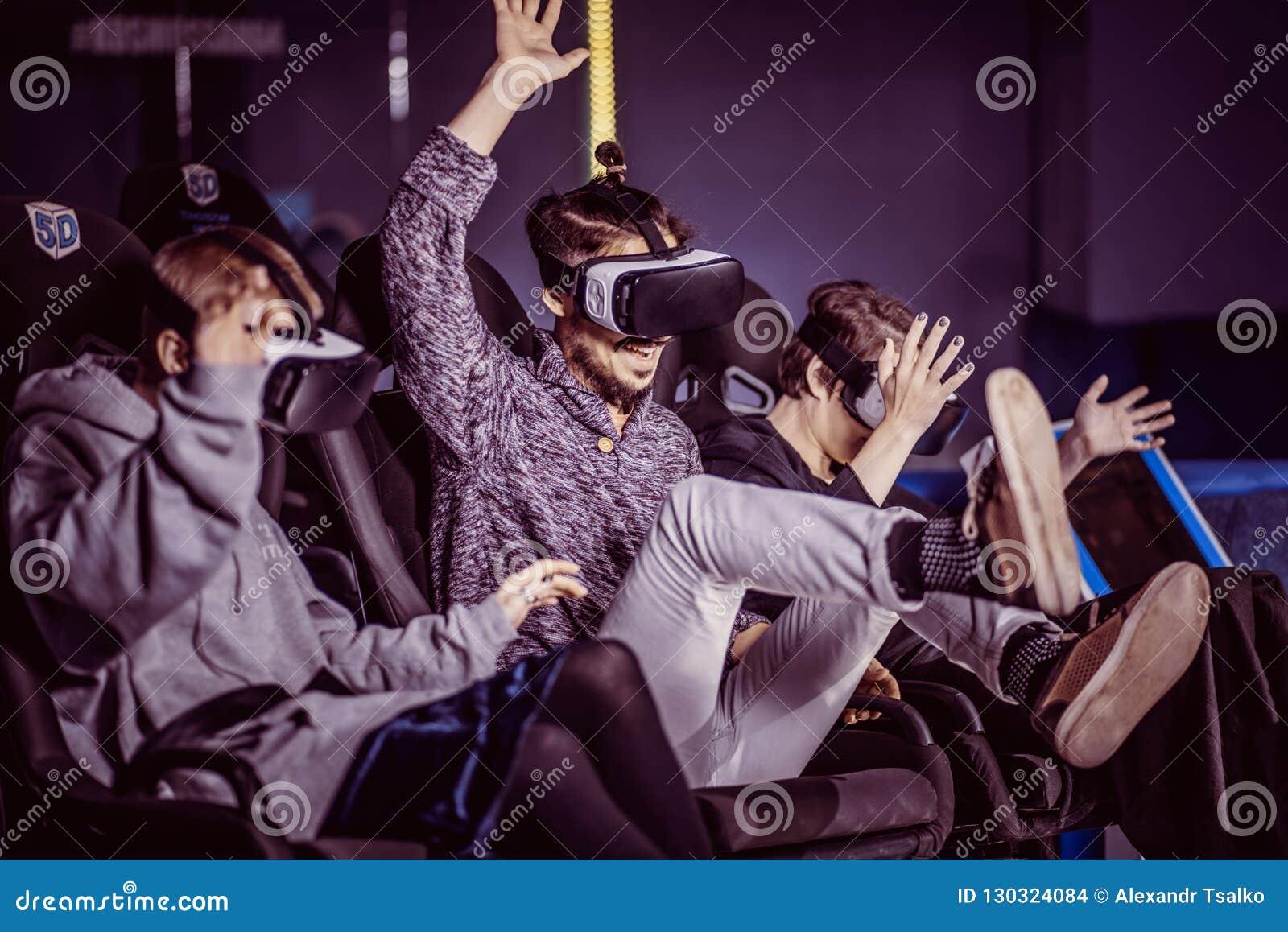 Amigos em vidros virtuais que olham filmes no cinema com sp