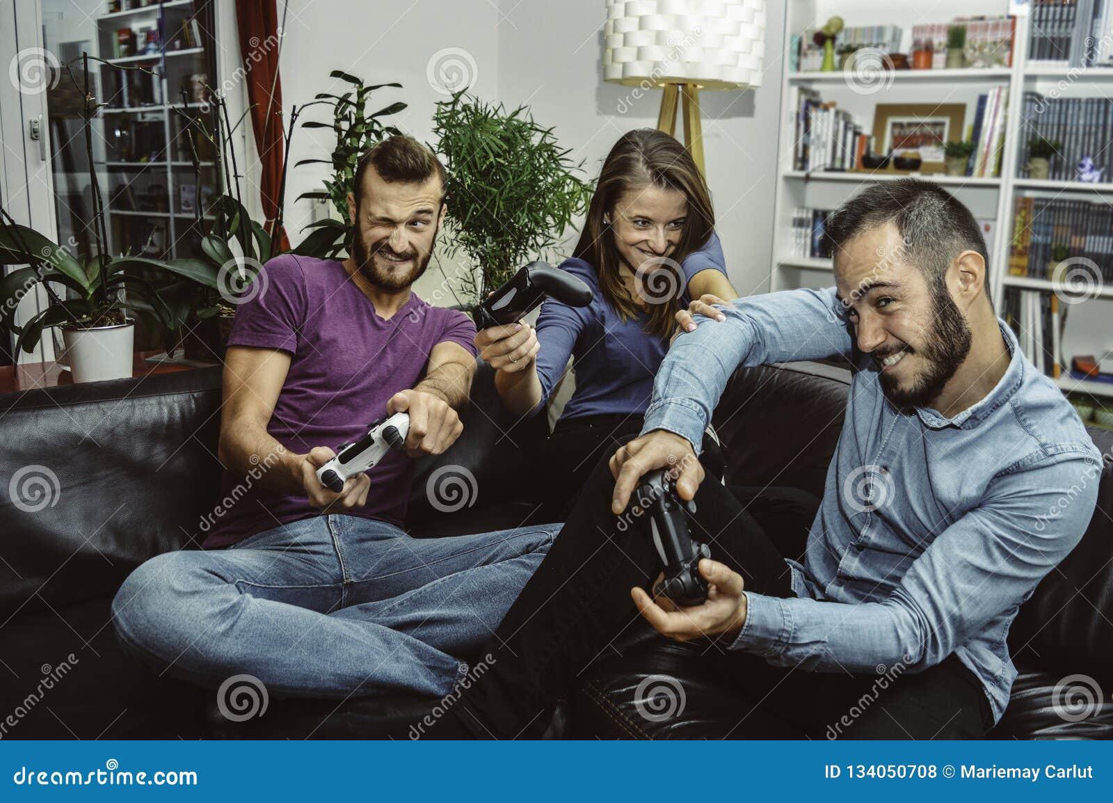 Amigos emocionados felices que juegan a los videojuegos en casa junto y que se divierten