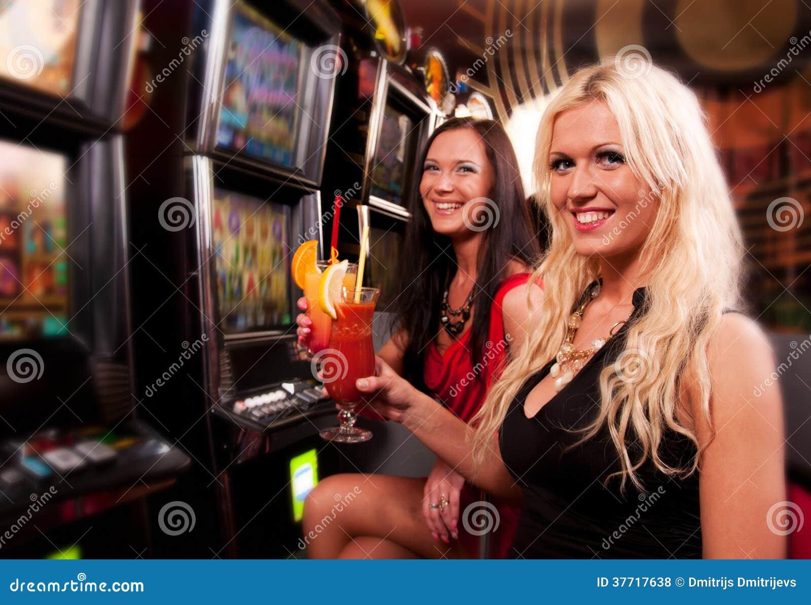 Amigos en casino en una máquina tragaperras