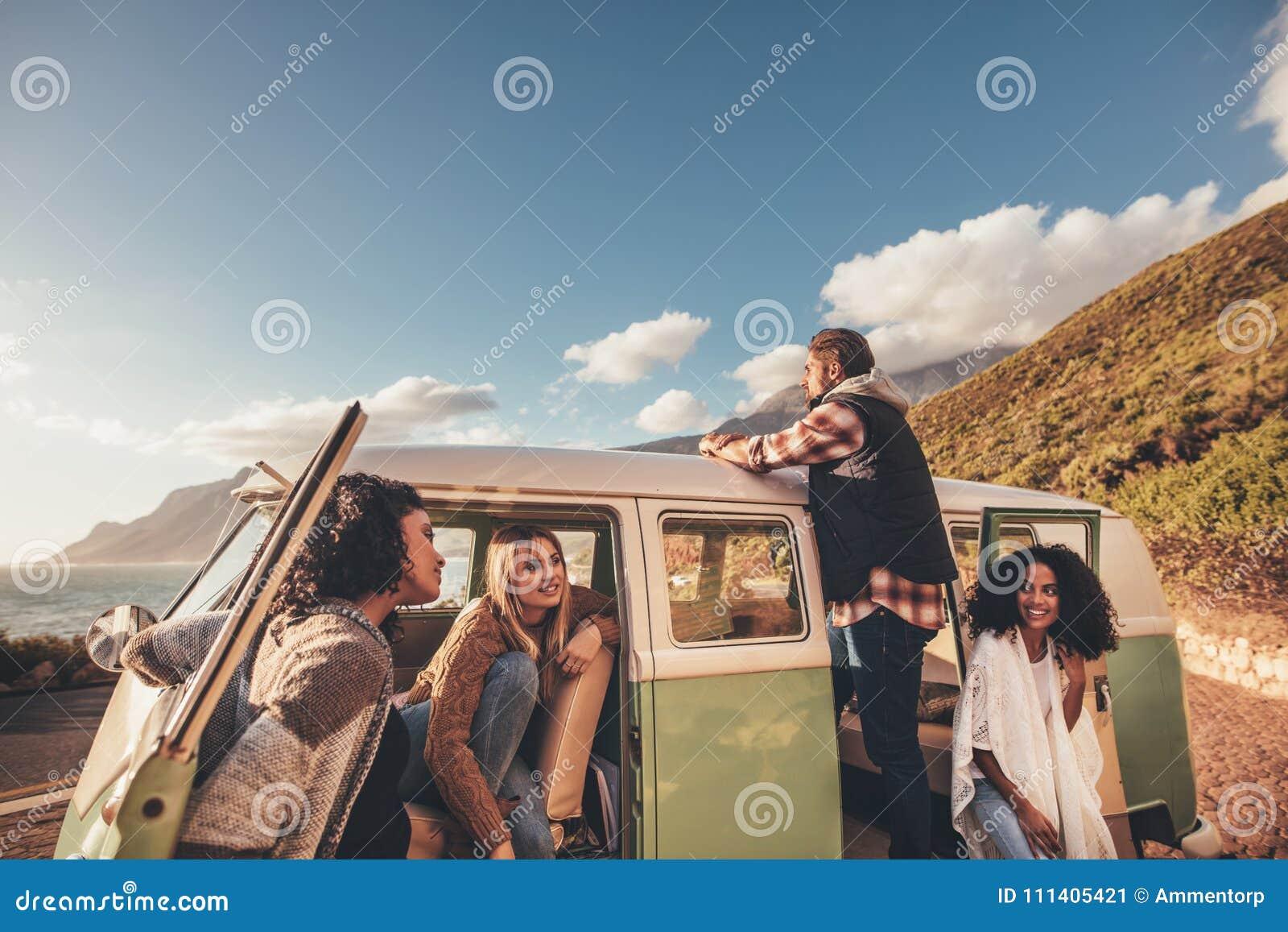 Amigos en el roadtrip que se relaja por la furgoneta