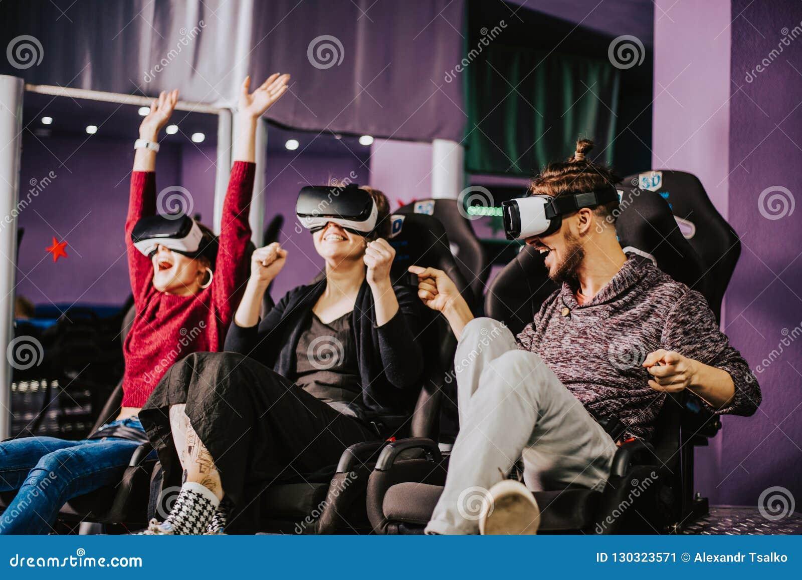 Amigos en vidrios virtuales que miran películas en el cine con el SP