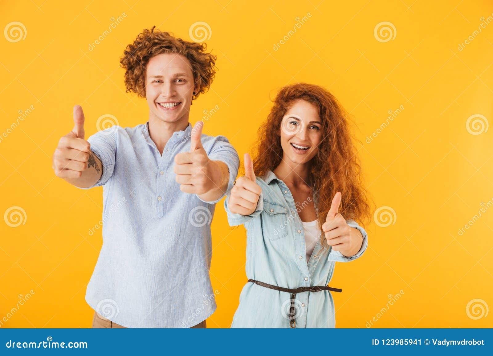 Amigos entusiasmado que amam os pares que mostram os polegares acima