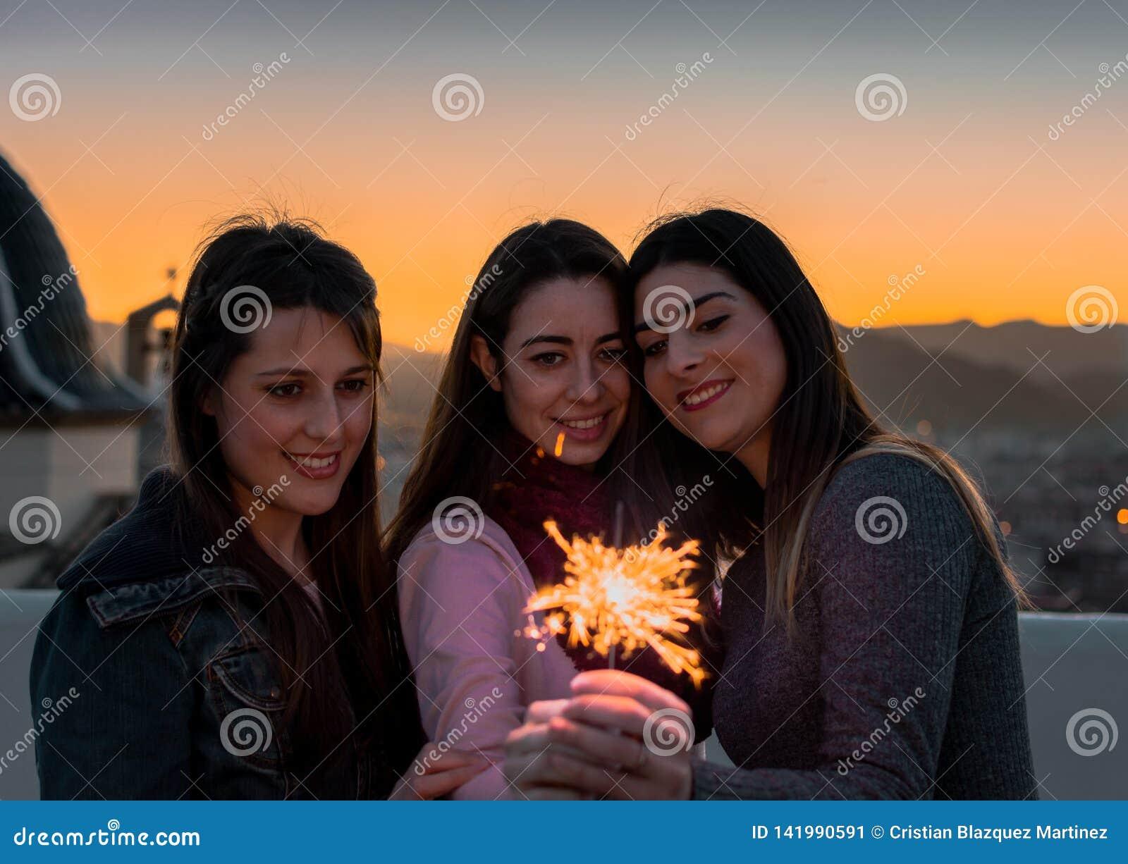 Amigos fêmeas com os chuveirinhos exteriores no por do sol