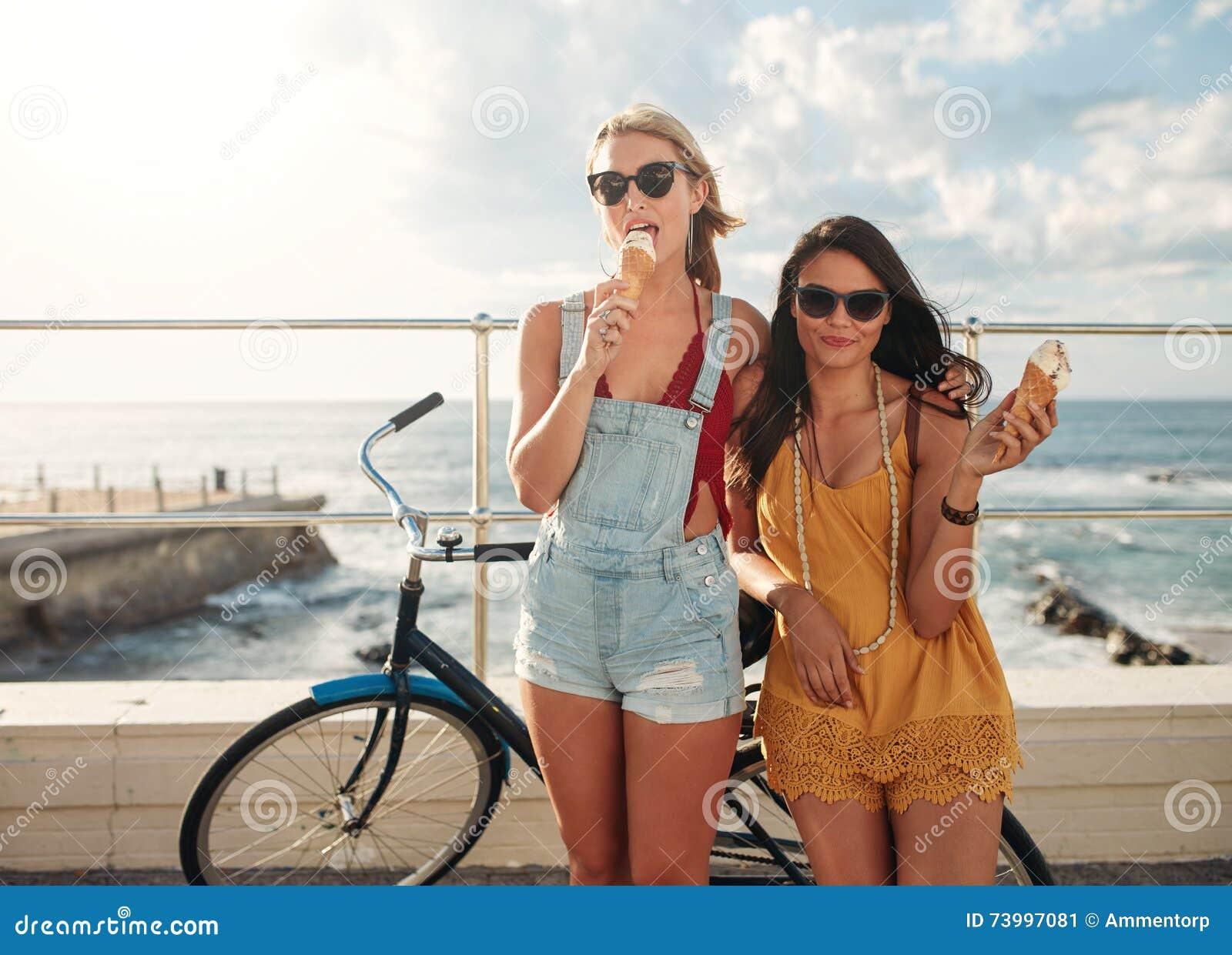 Amigos fêmeas com uma bicicleta que comem o gelado
