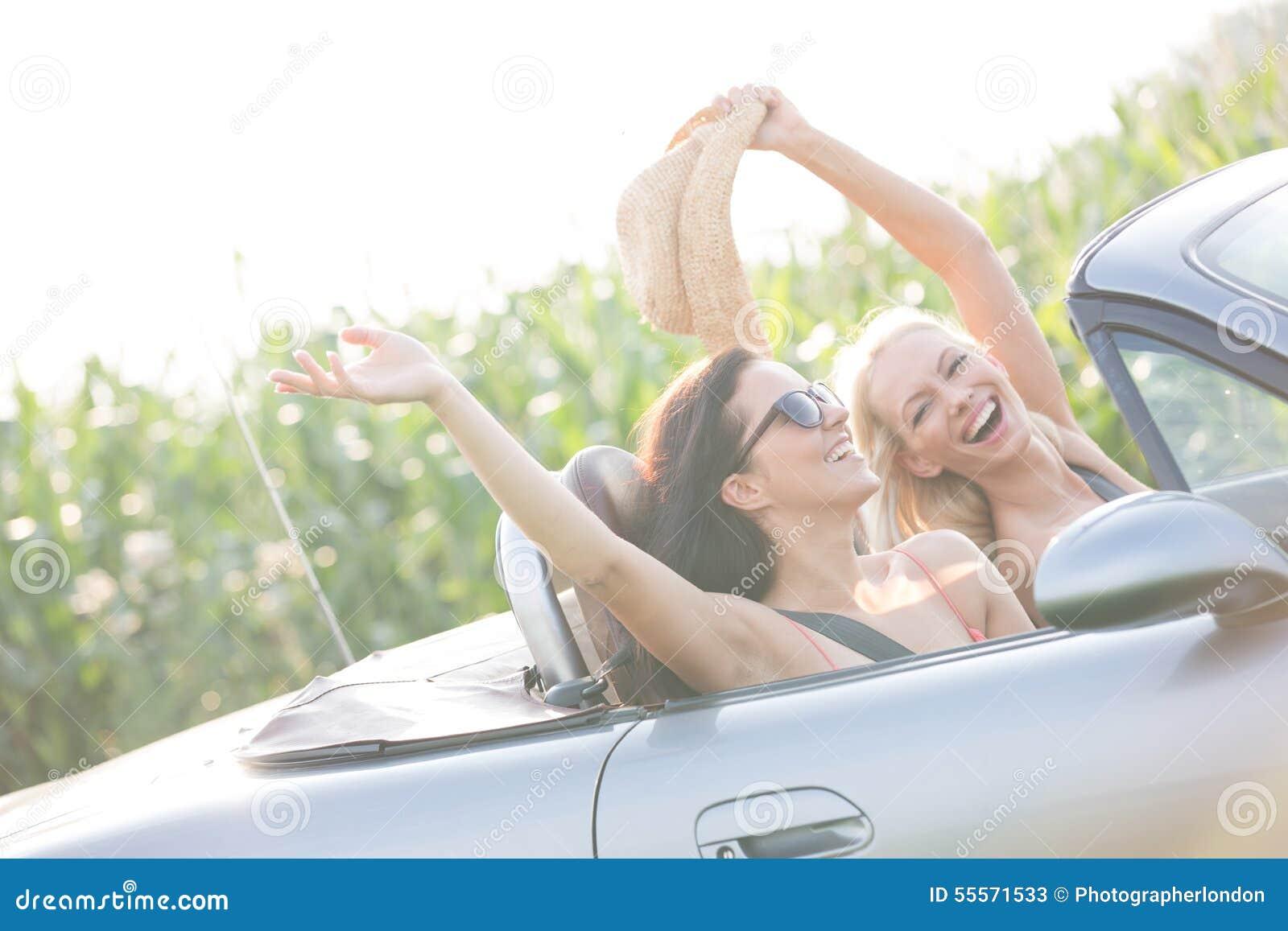 Amigos fêmeas entusiasmado que apreciam a viagem por estrada no convertible no dia ensolarado