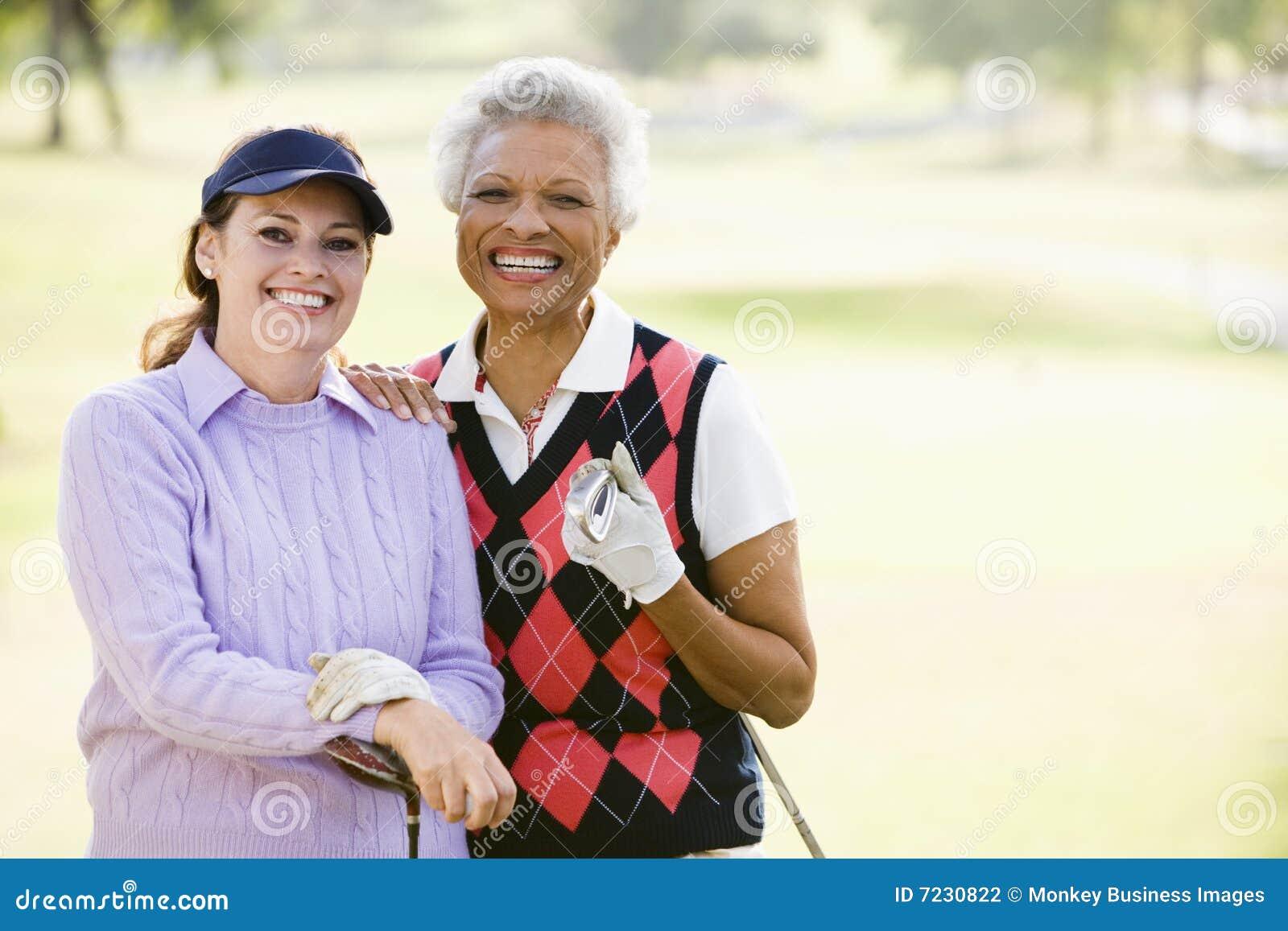 Amigos fêmeas que apreciam um jogo do golfe