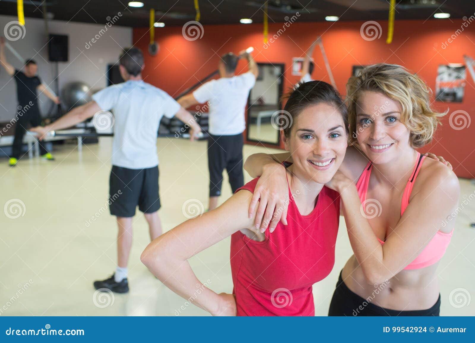 Amigos fêmeas que exercitam no gym que sorri alegremente