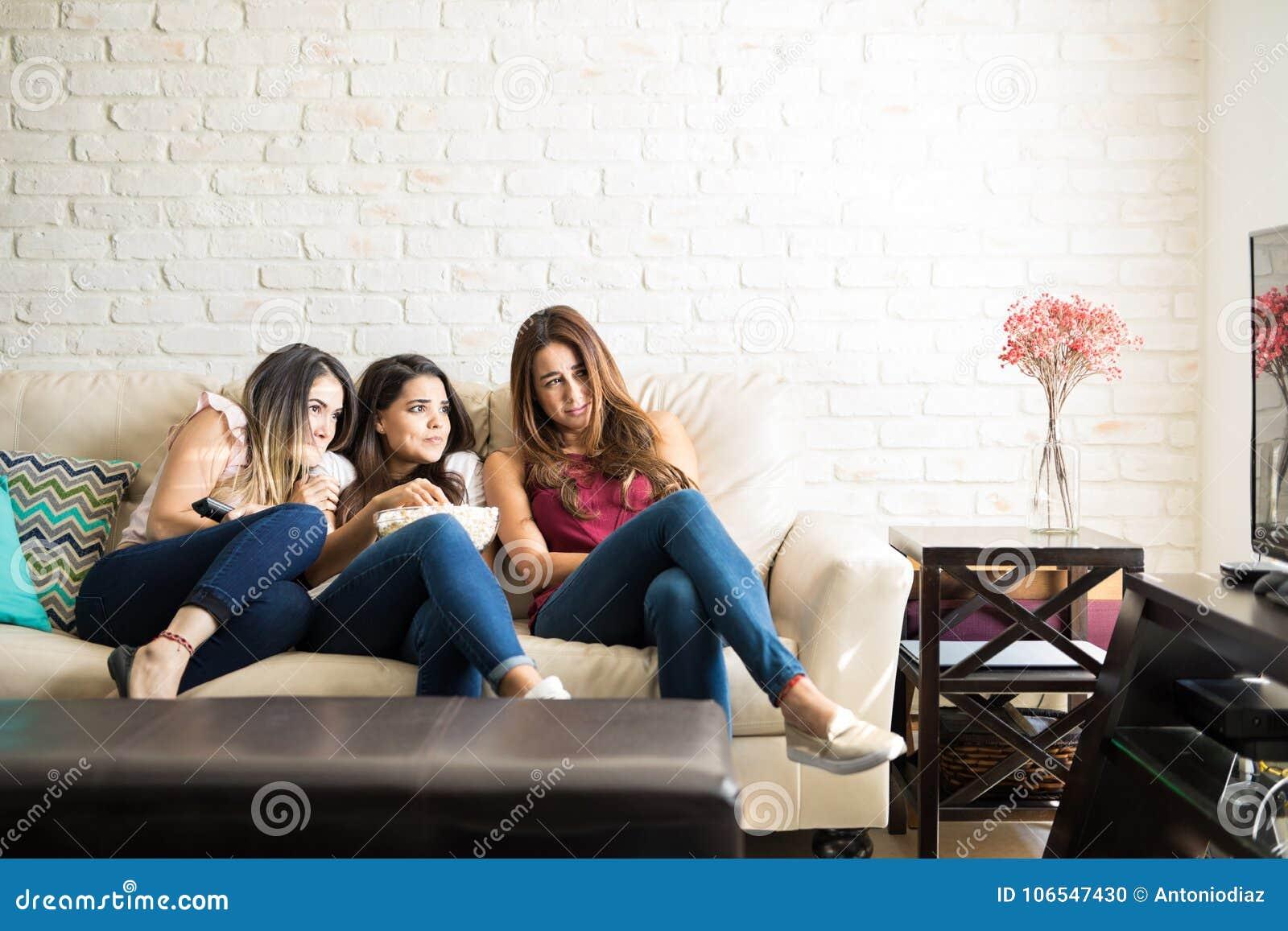 Amigos fêmeas que olham um filme de terror