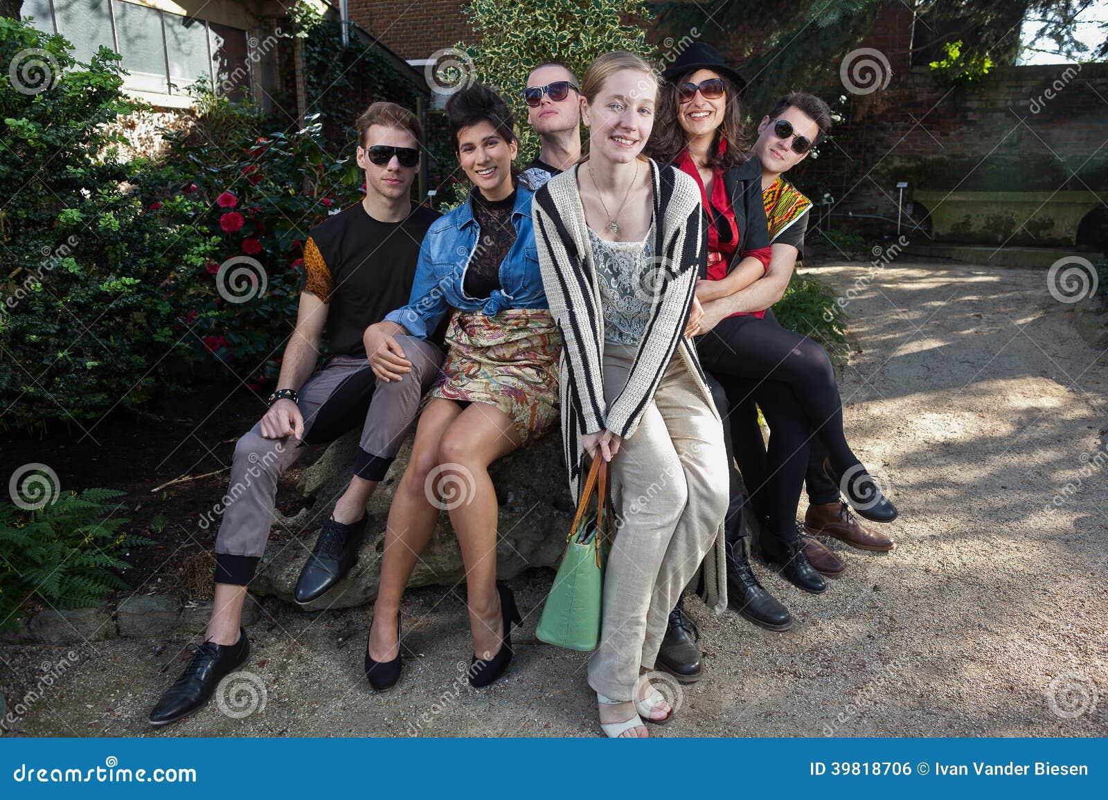 Amigos felices en roca en parque