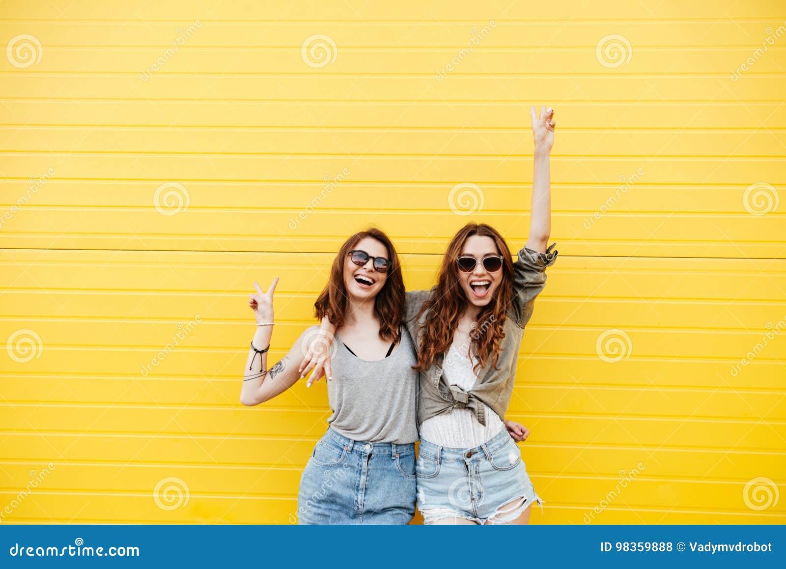 Amigos felices jovenes de las mujeres que se colocan sobre la pared amarilla