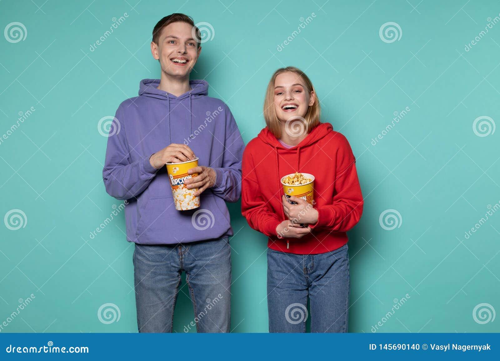 Amigos felices, muchacha rubia hermosa e individuo en sudadera con capucha púrpura mirando una película de la comedia con palomit