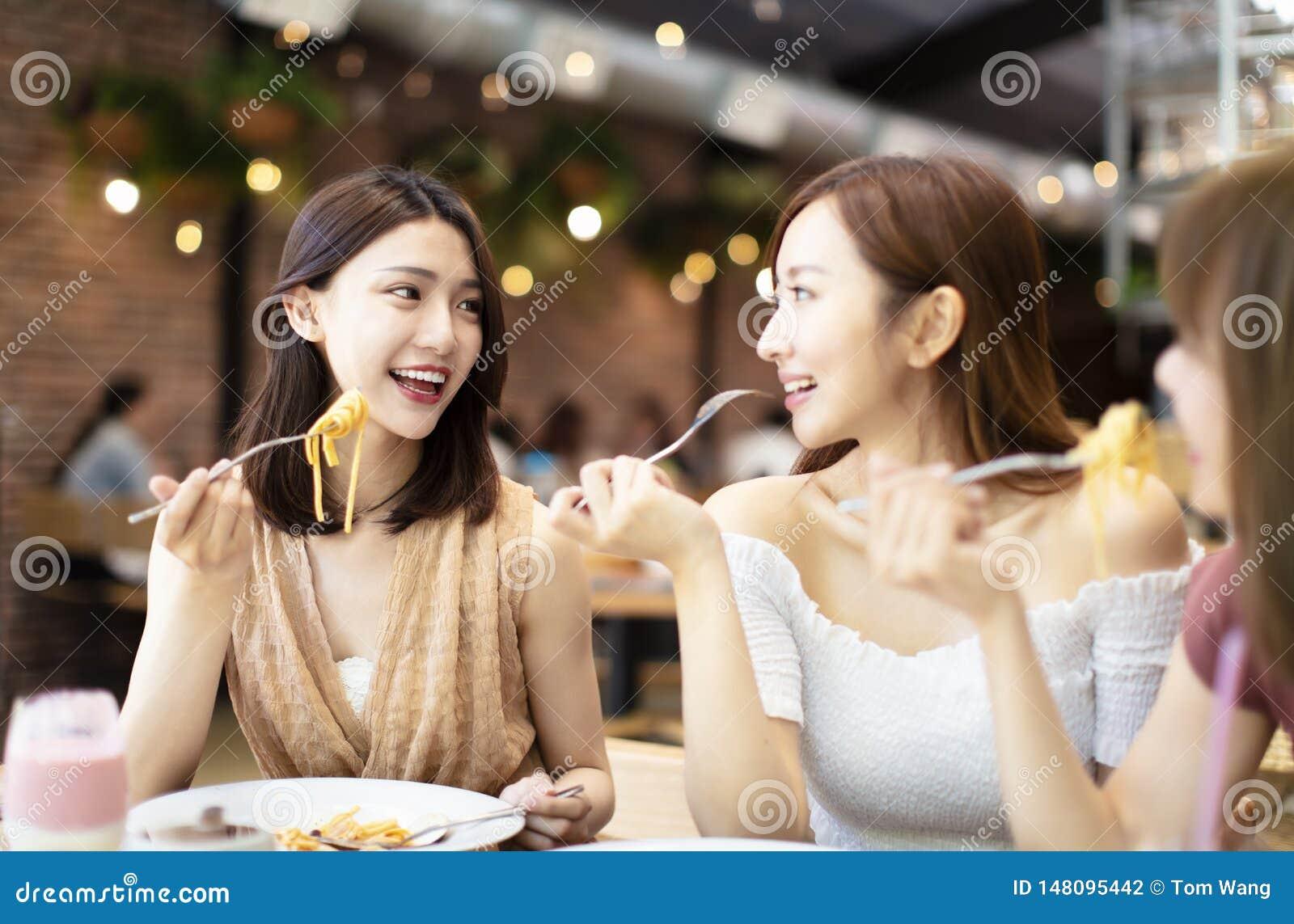 Amigos felices que cenan en el restaurante