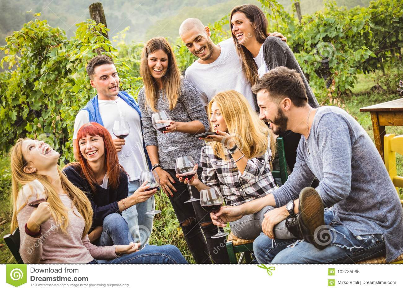 Amigos felices que se divierten al aire libre - gente joven que bebe el vino rojo en el viñedo del lagar