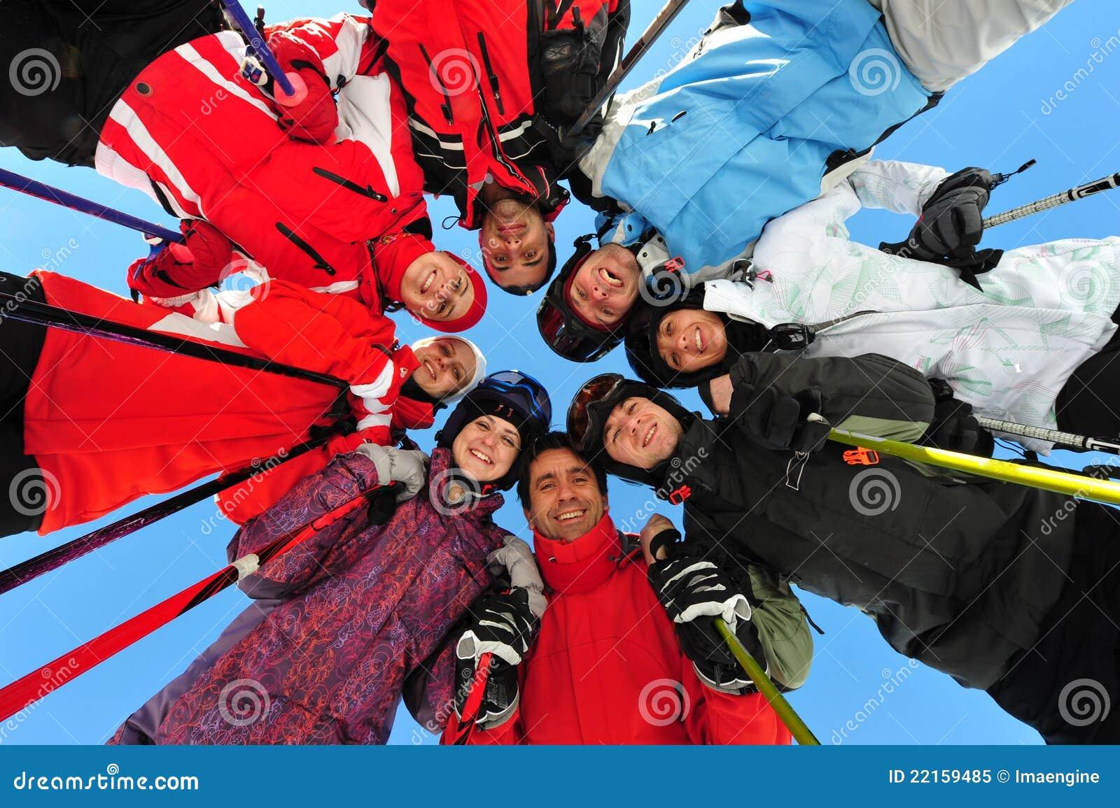 Amigos felices que sienten grandes en la estación del esquí