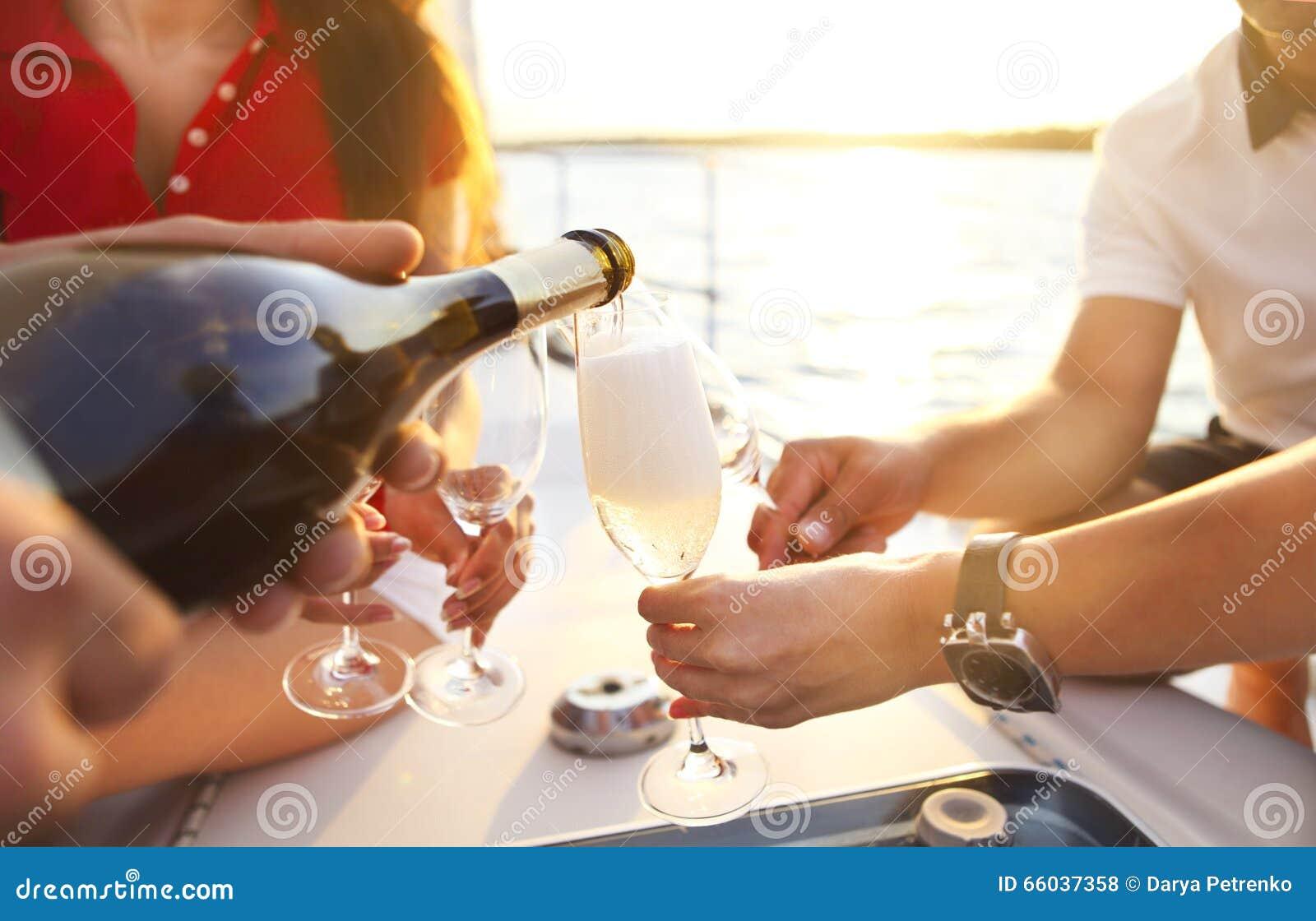 Amigos felizes com vidros do champanhe no iate
