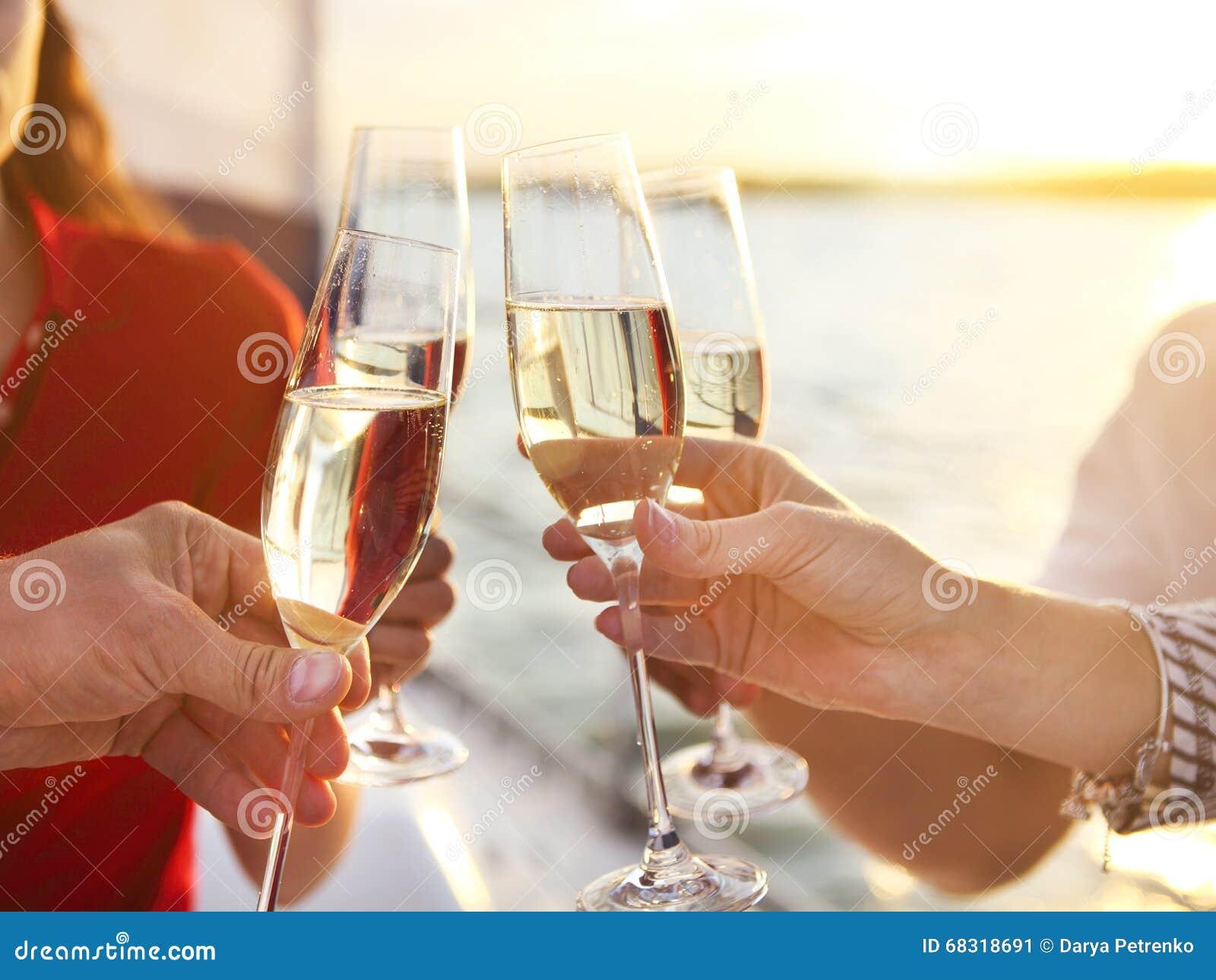 Amigos felizes com vidros do champanhe no iate Férias, trav