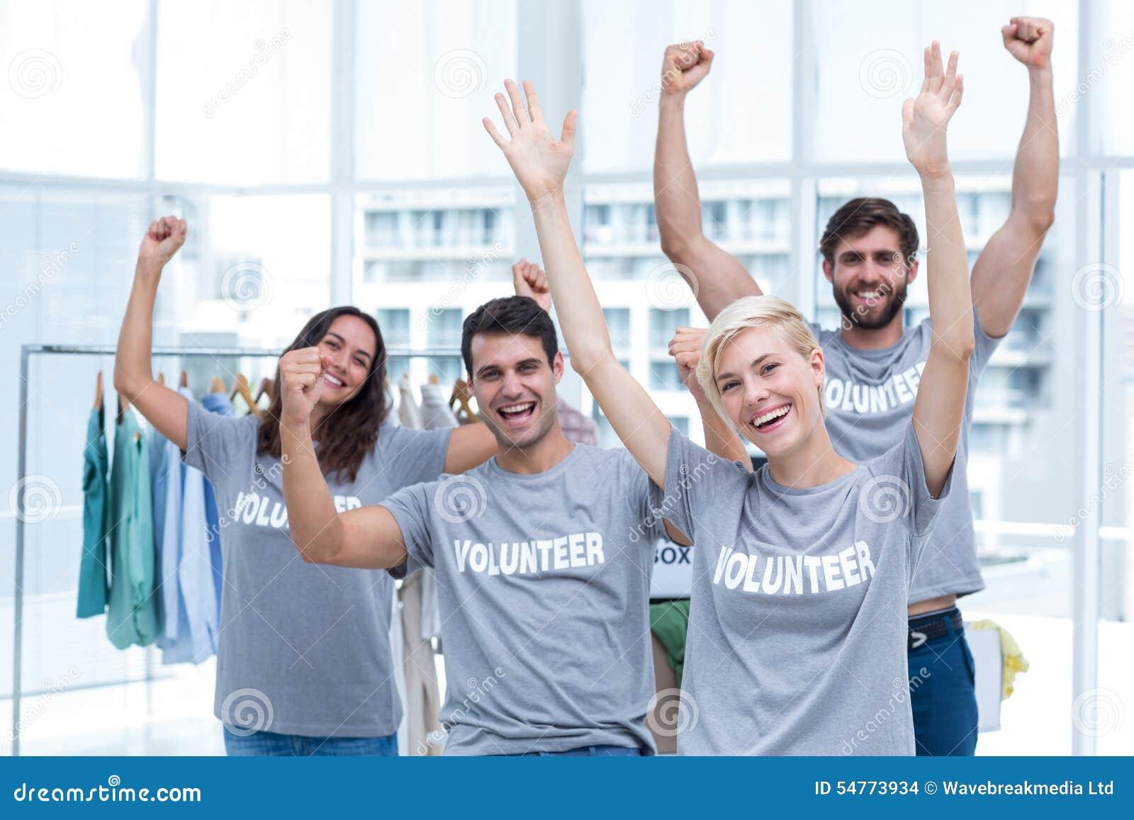 Amigos felizes dos voluntários que aumentam os braços