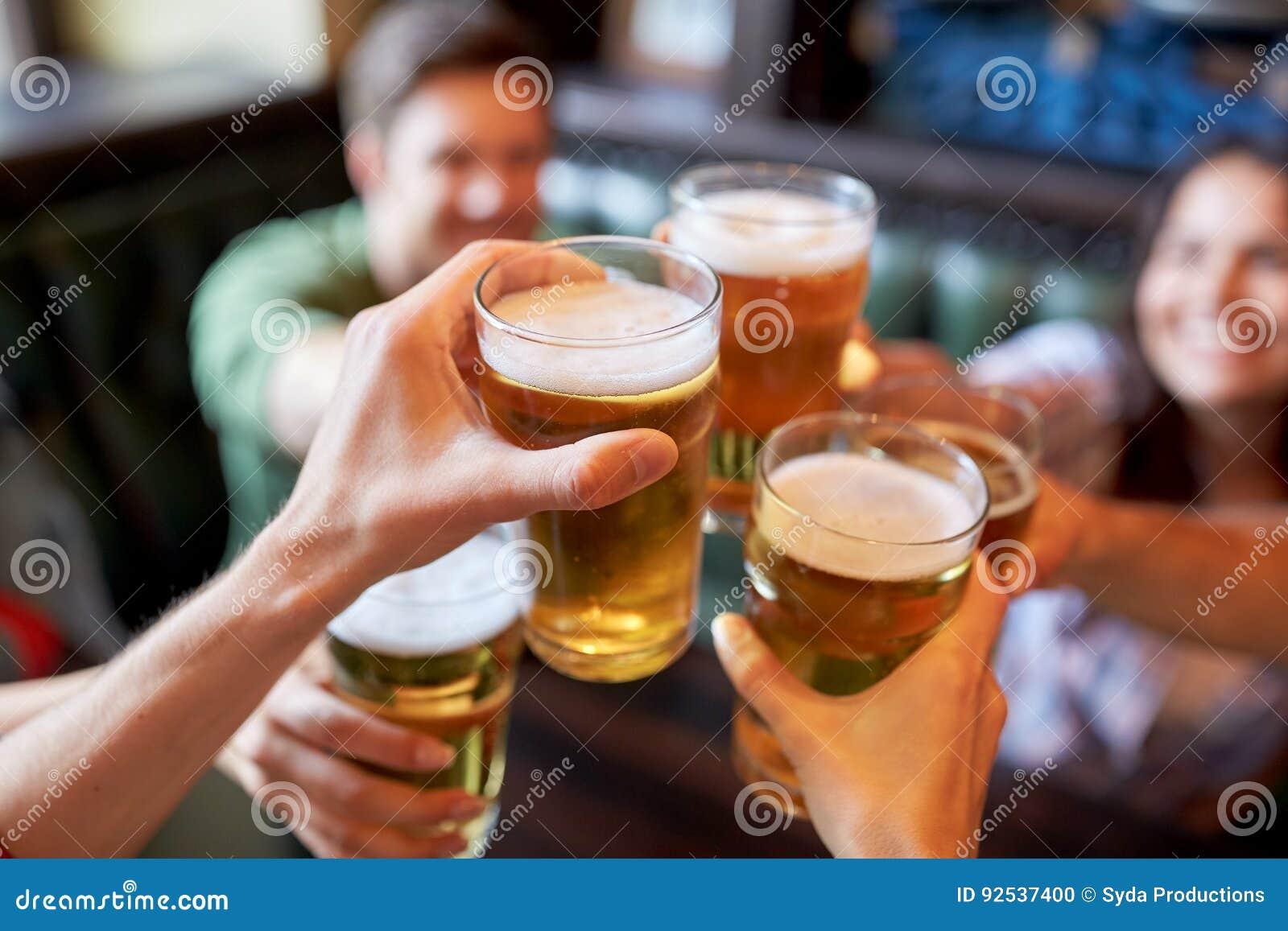 Amigos felizes que bebem a cerveja na barra ou no bar