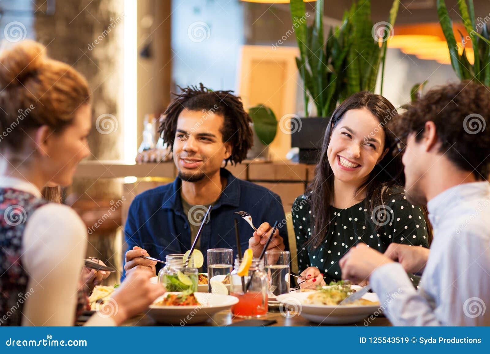 Amigos felizes que comem no restaurante