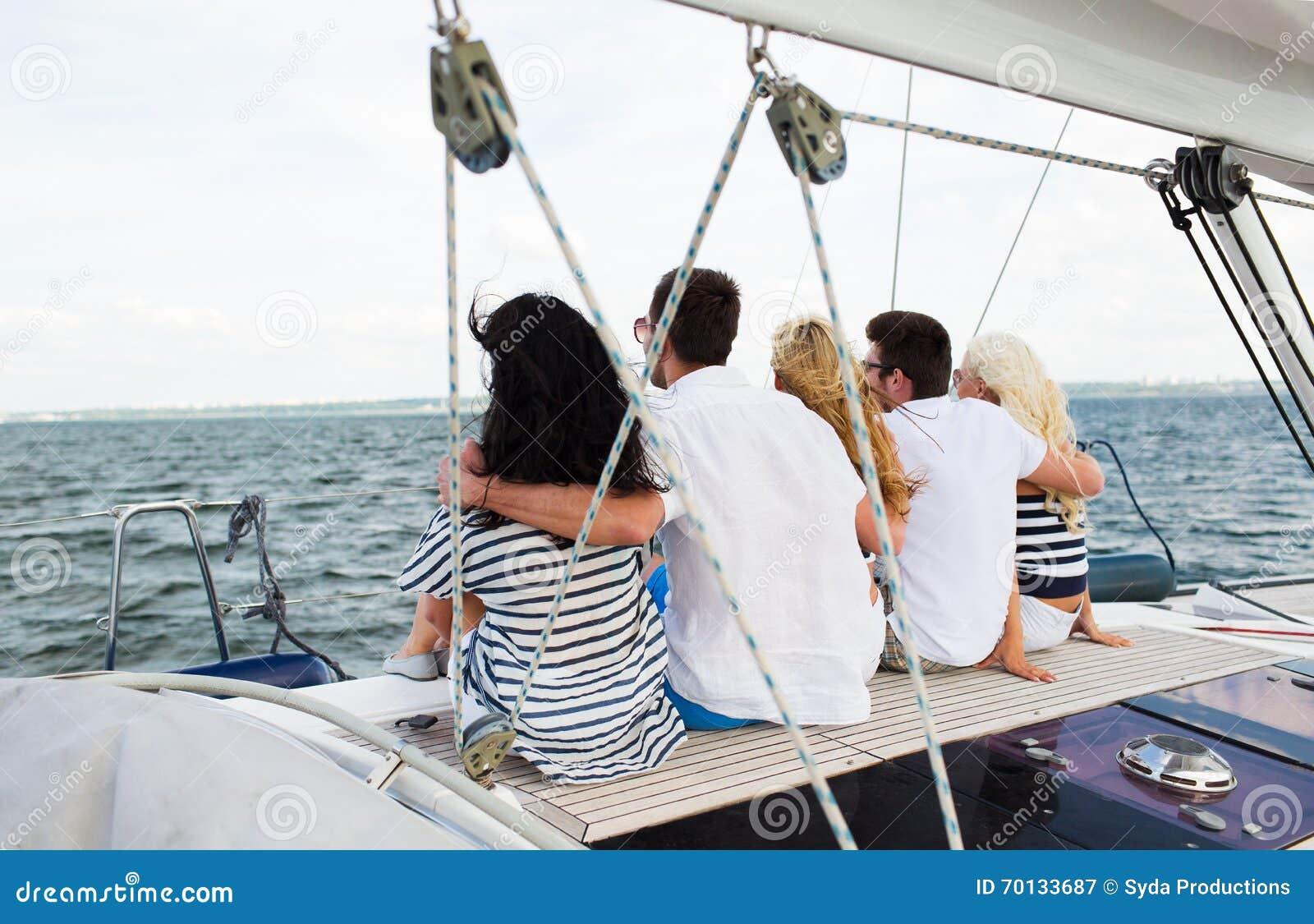 Amigos felizes que navegam e que sentam-se na plataforma do iate