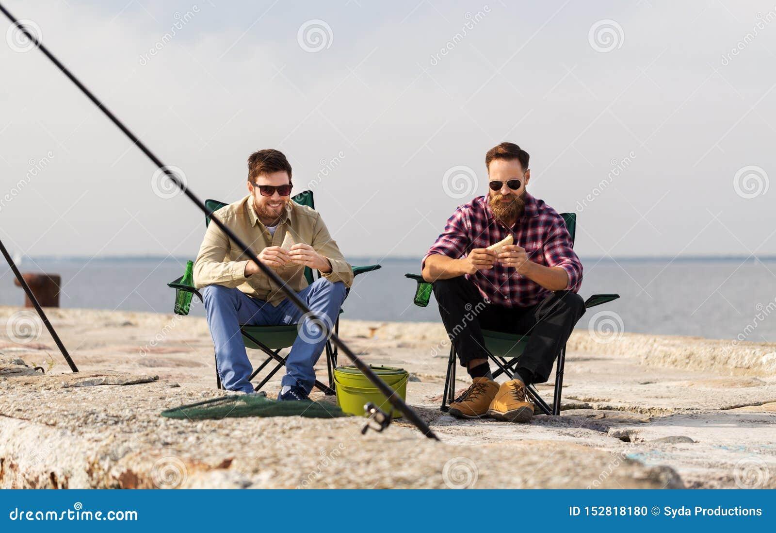 Amigos felizes que pescam e que comem sandu?ches