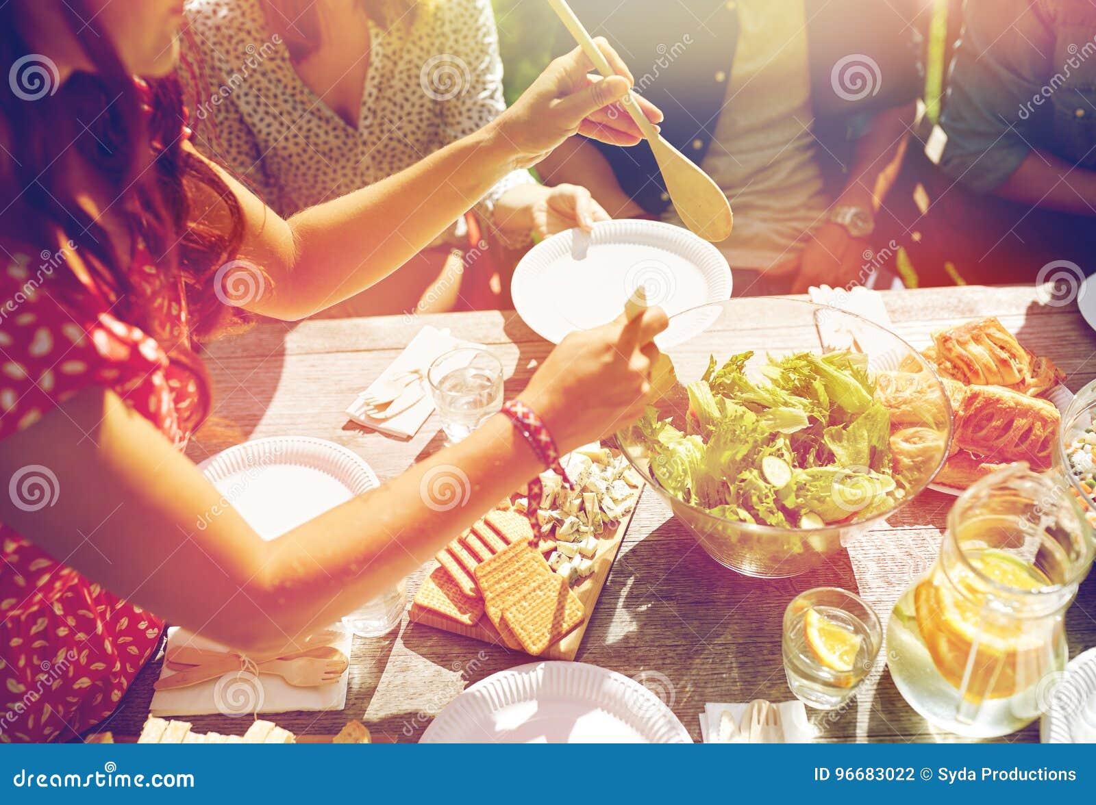 Amigos felizes que têm o jantar no partido do verão