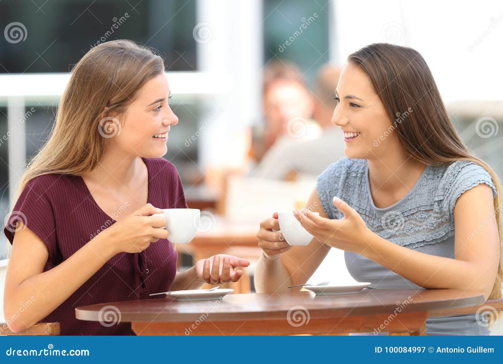Amigos felizes que têm uma conversação em uma barra
