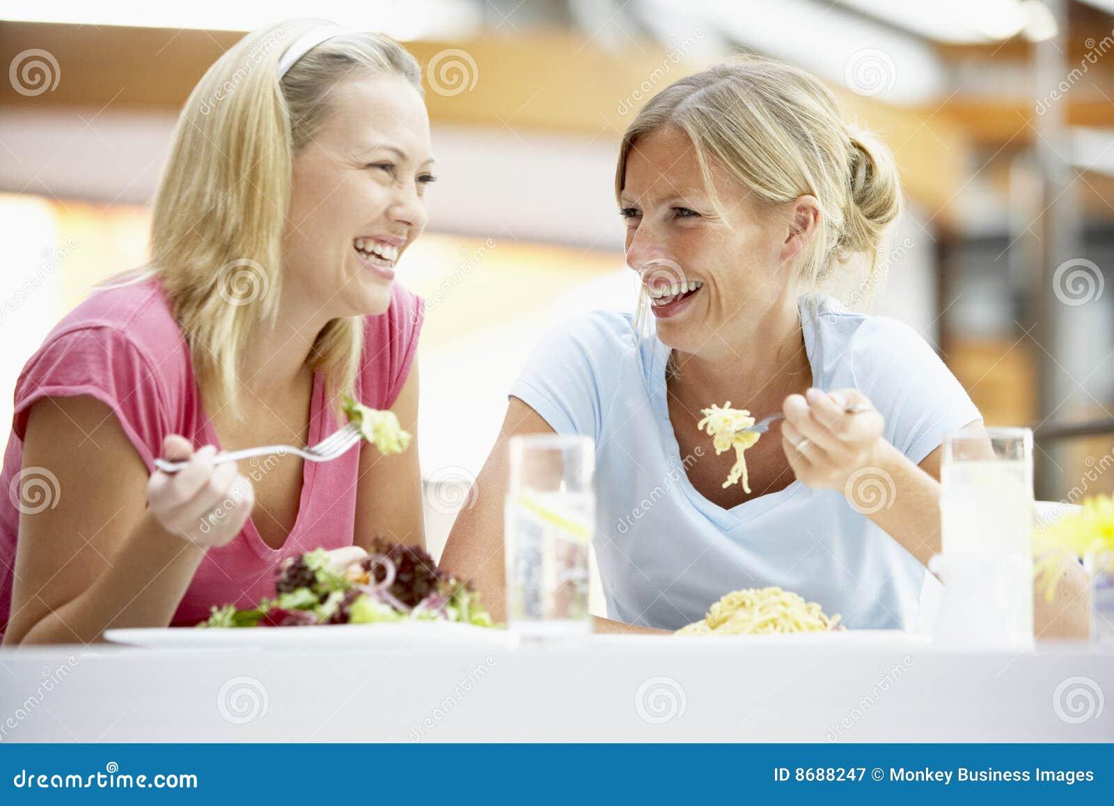 Amigos femeninos que almuerzan junto en la alameda