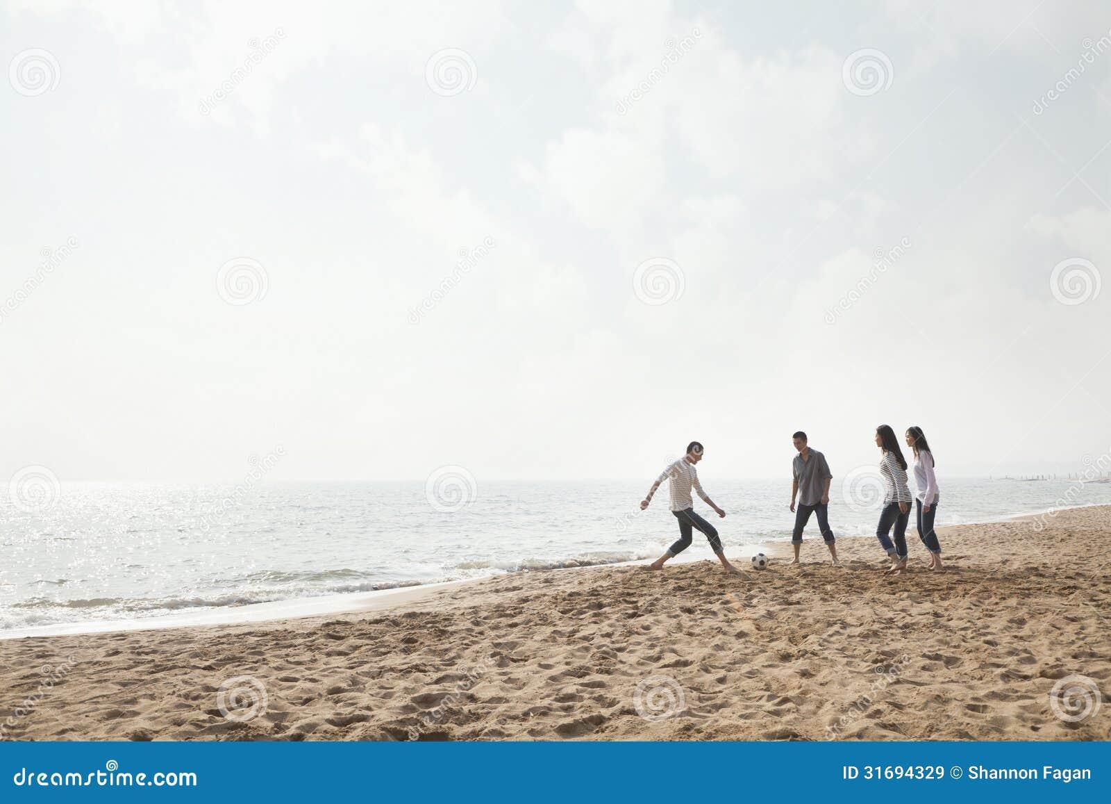 Amigos jovenes que juegan a fútbol en la playa