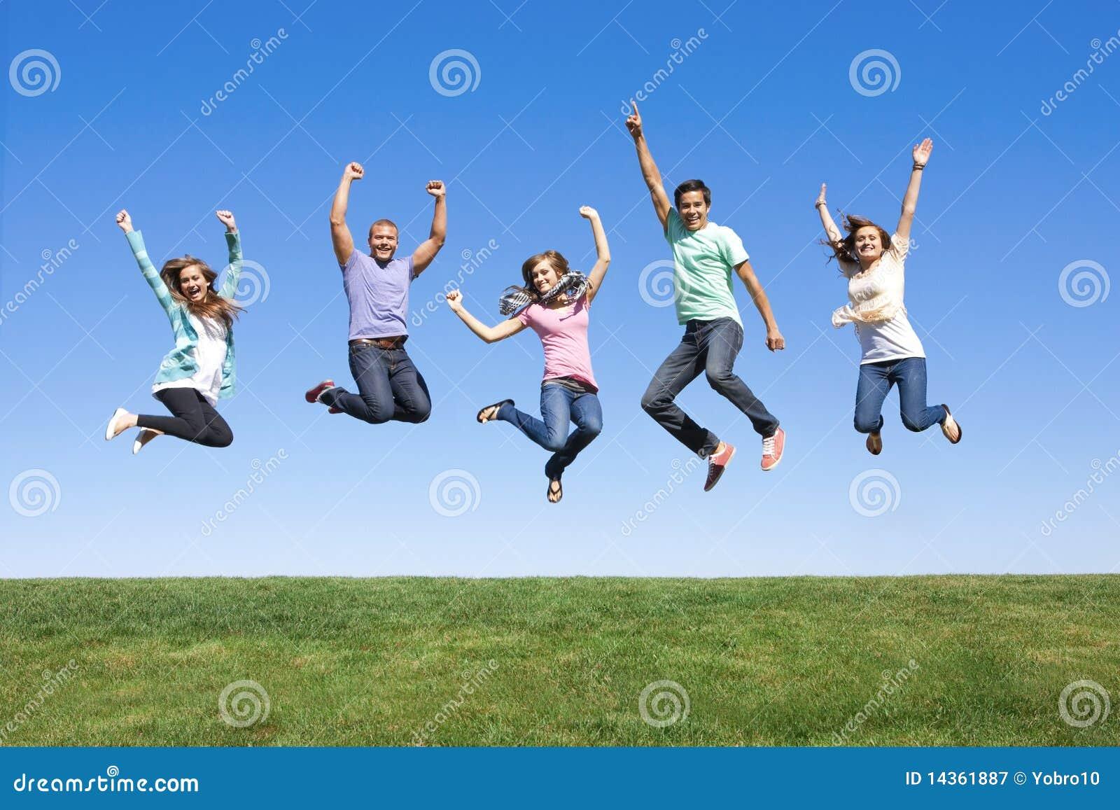 Amigos jovenes que saltan y que se divierten