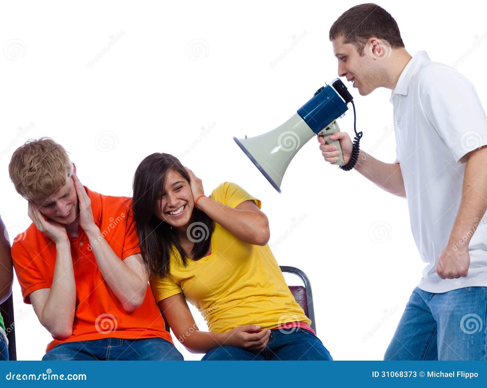 Amigos jovenes que son gritados en cerca un megáfono
