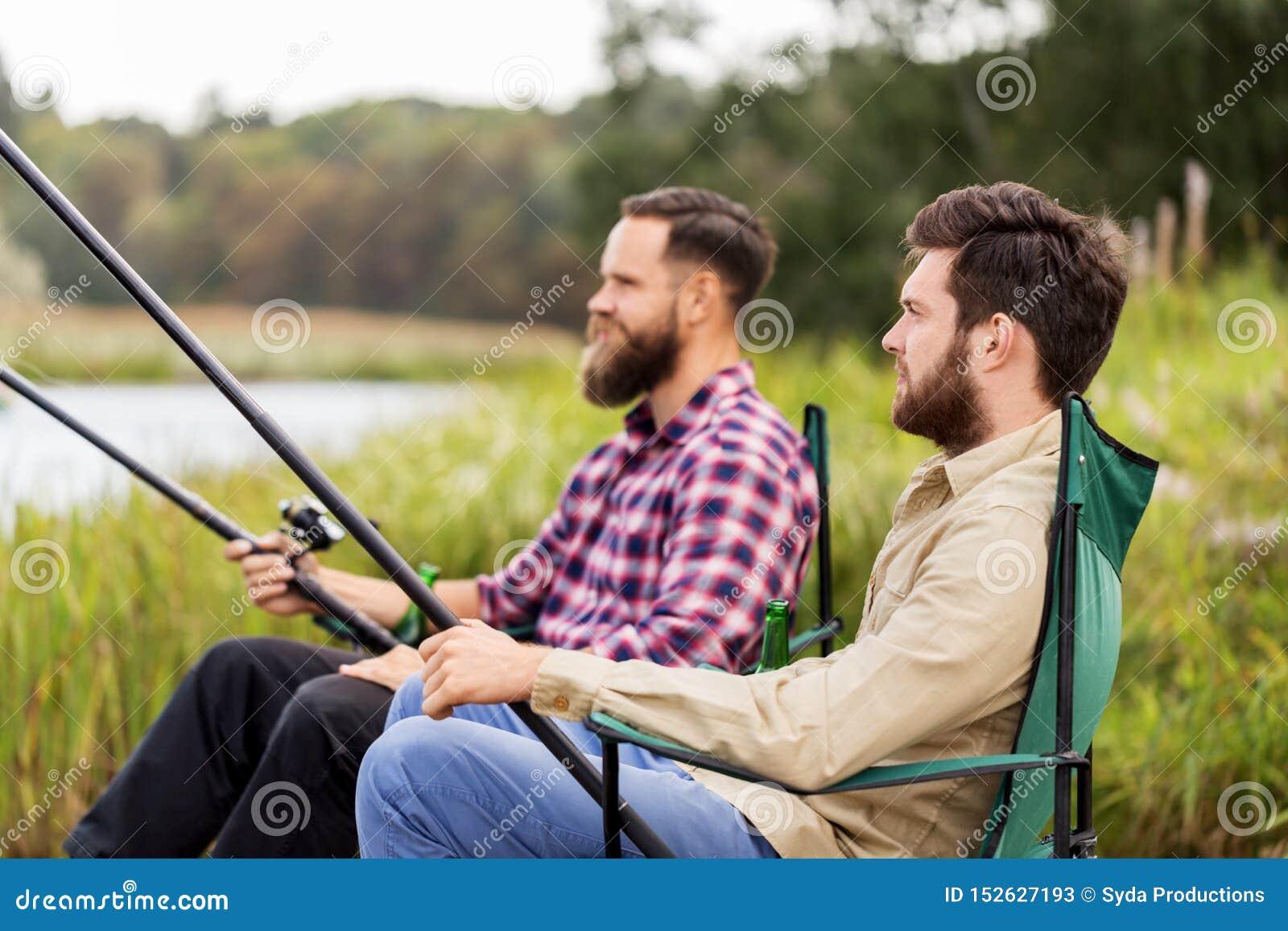 Amigos masculinos com as varas de pesca no lago