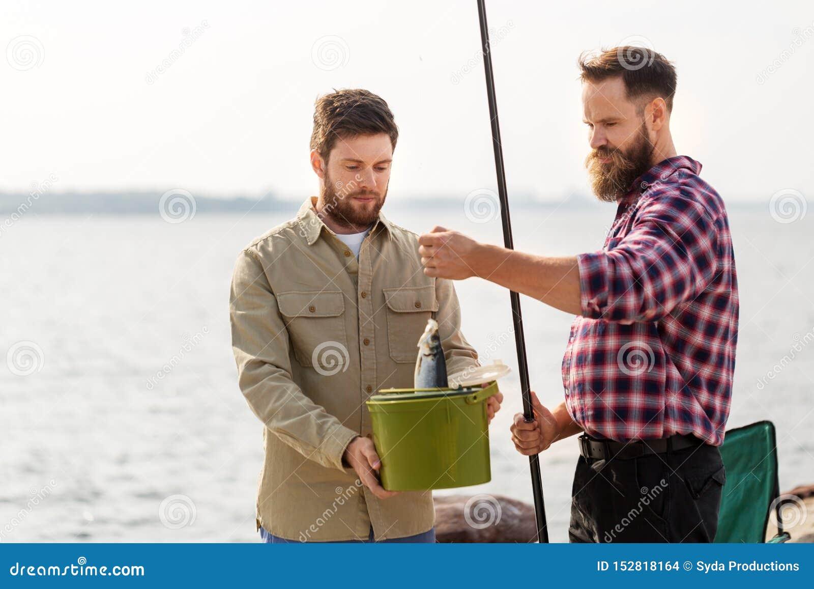 Amigos masculinos com peixes e varas de pesca no cais