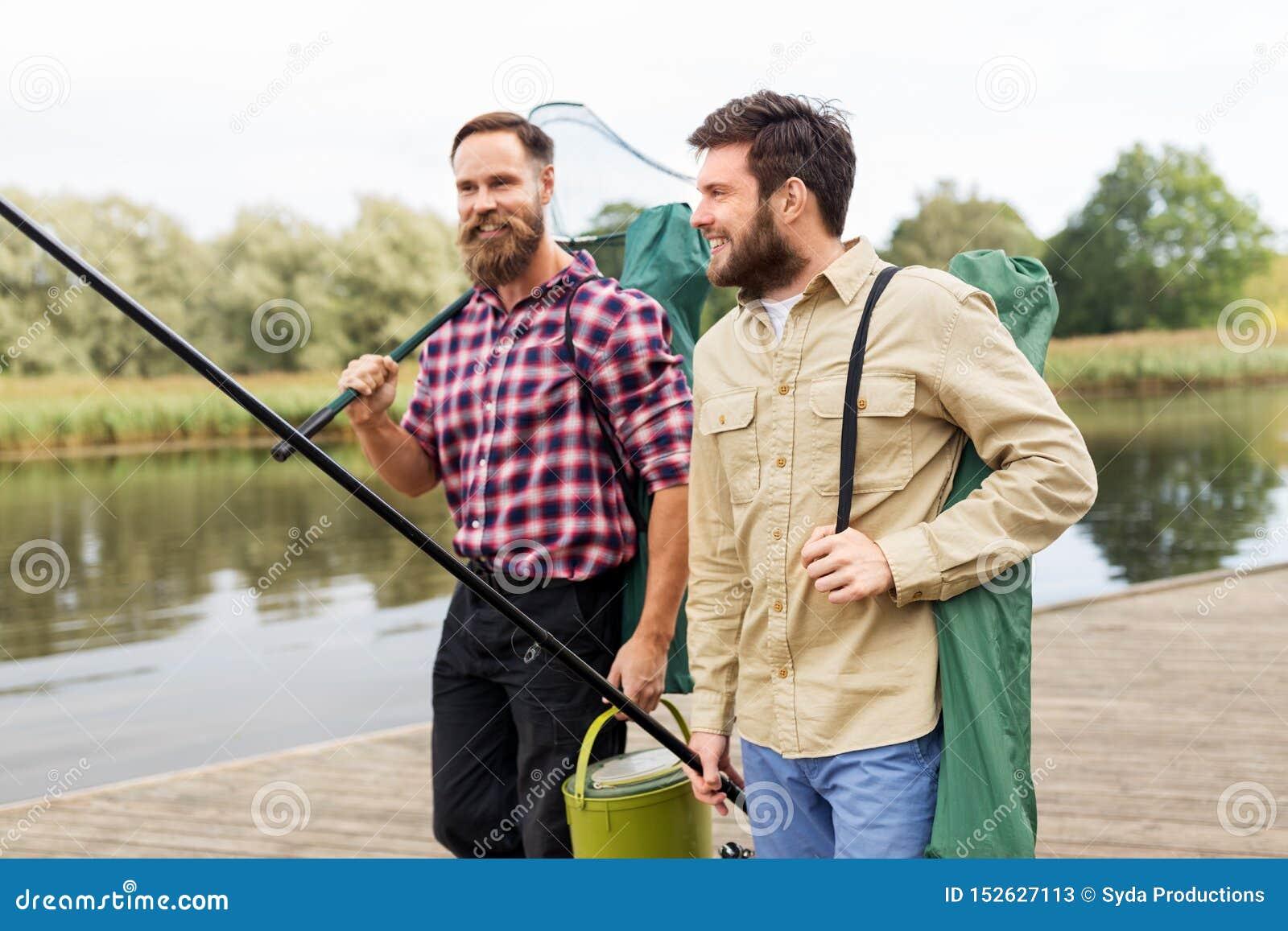 Amigos masculinos com rede e varas de pesca no lago