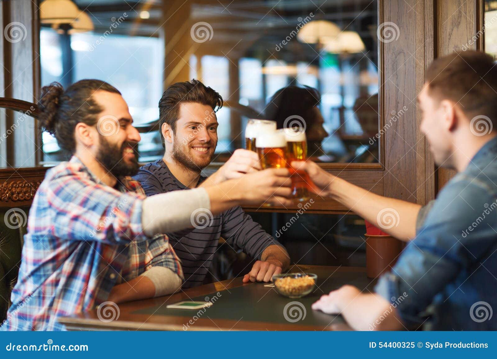 Amigos masculinos felices que beben la cerveza en la barra o el pub
